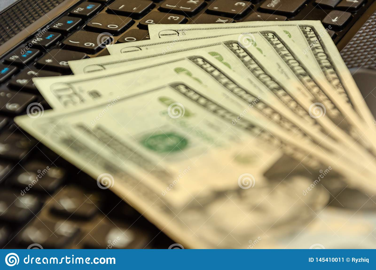 Money cash banknotes on laptop keyboard. American dollars