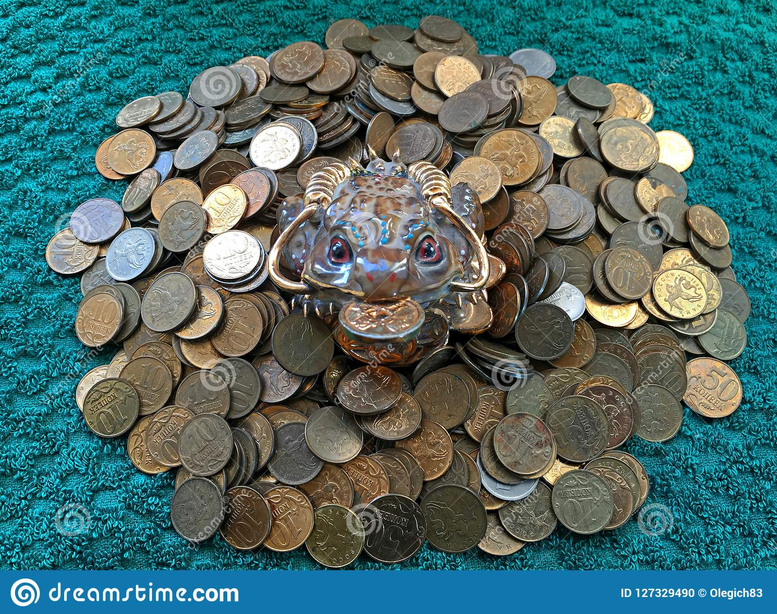 Money frog sitting on coins