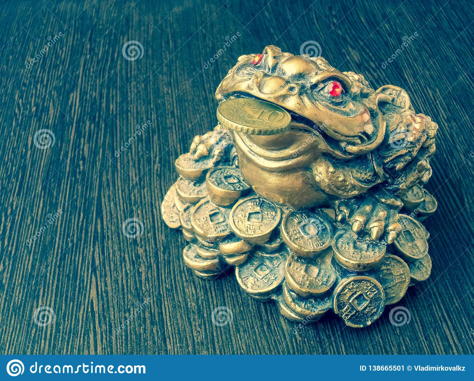 Money frog on a wooden table with a coin in its mouth