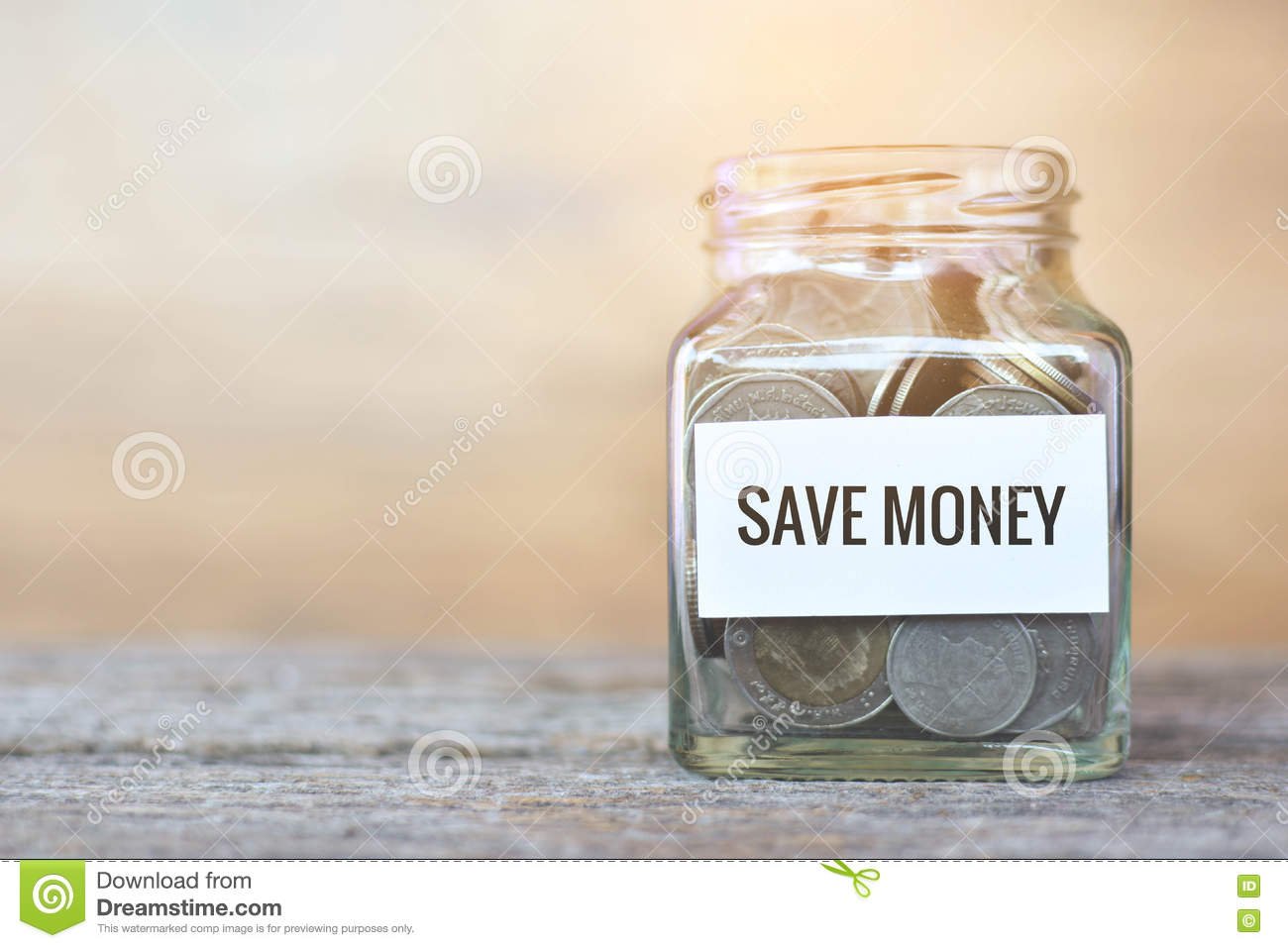 Money in a glass jar with `save money` word