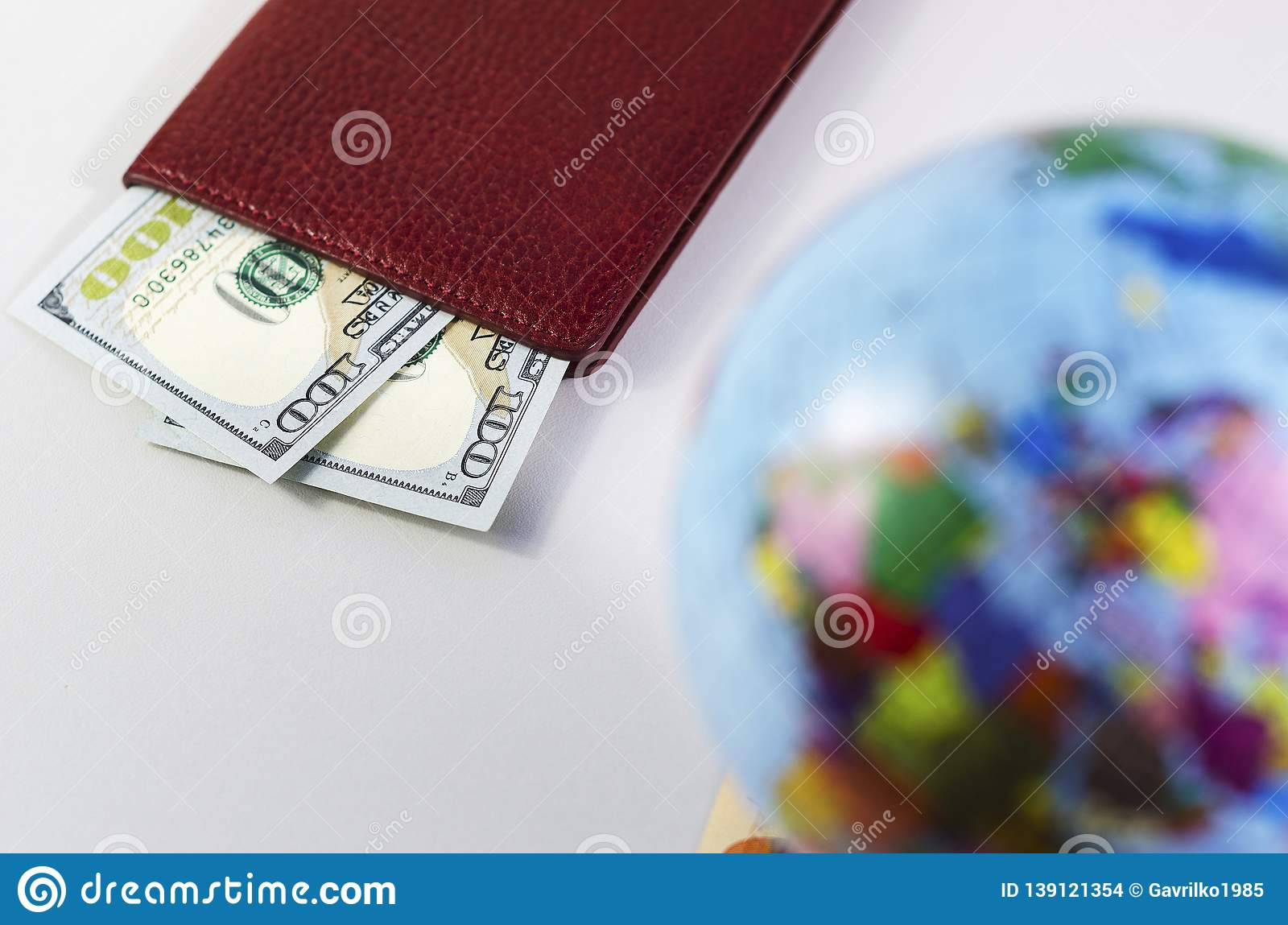 Money inside the passport and the globe is out of focus