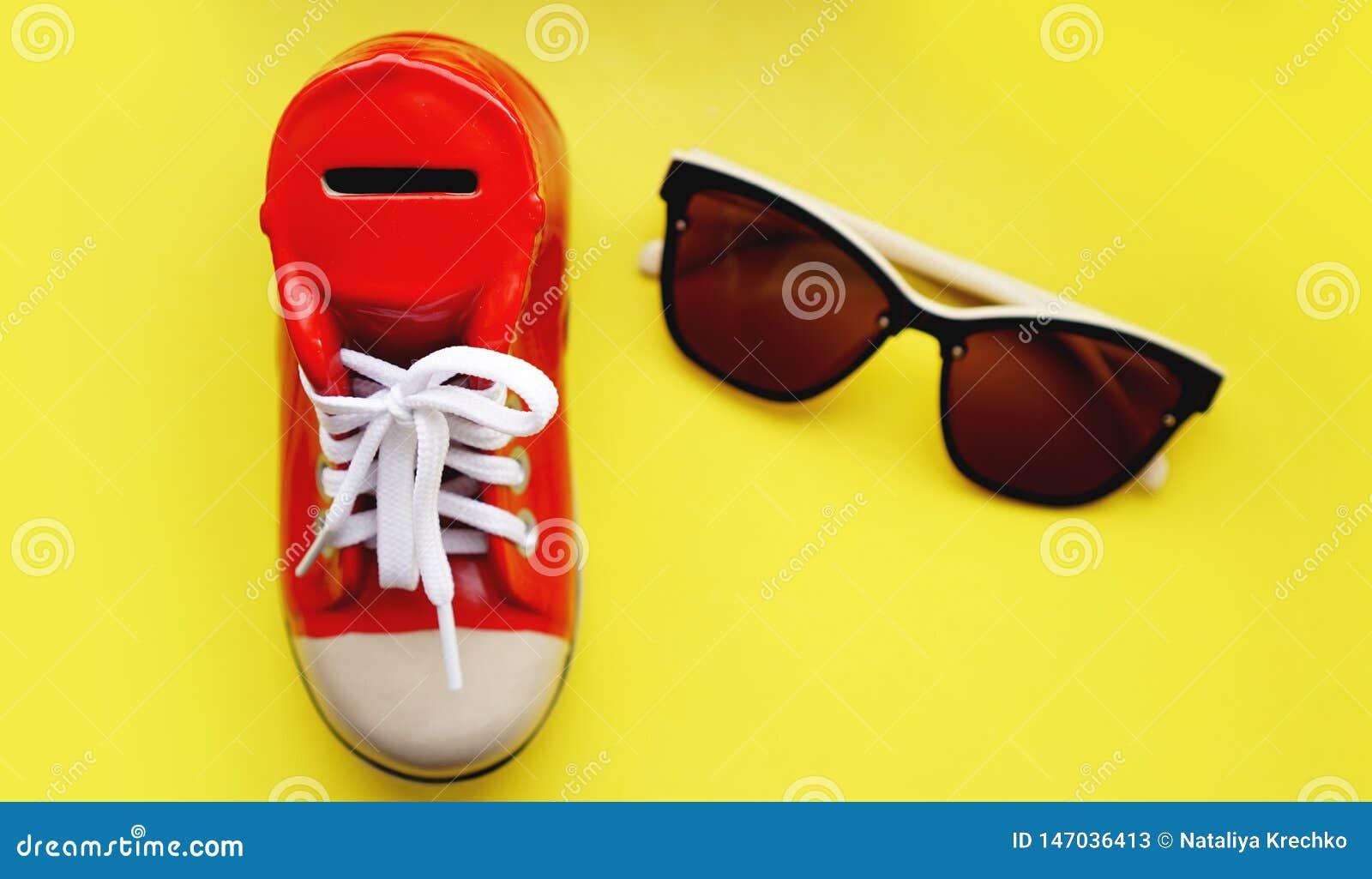Moneybox bajo la forma de zapatillas de deporte Gafas de sol en un fondo amarillo