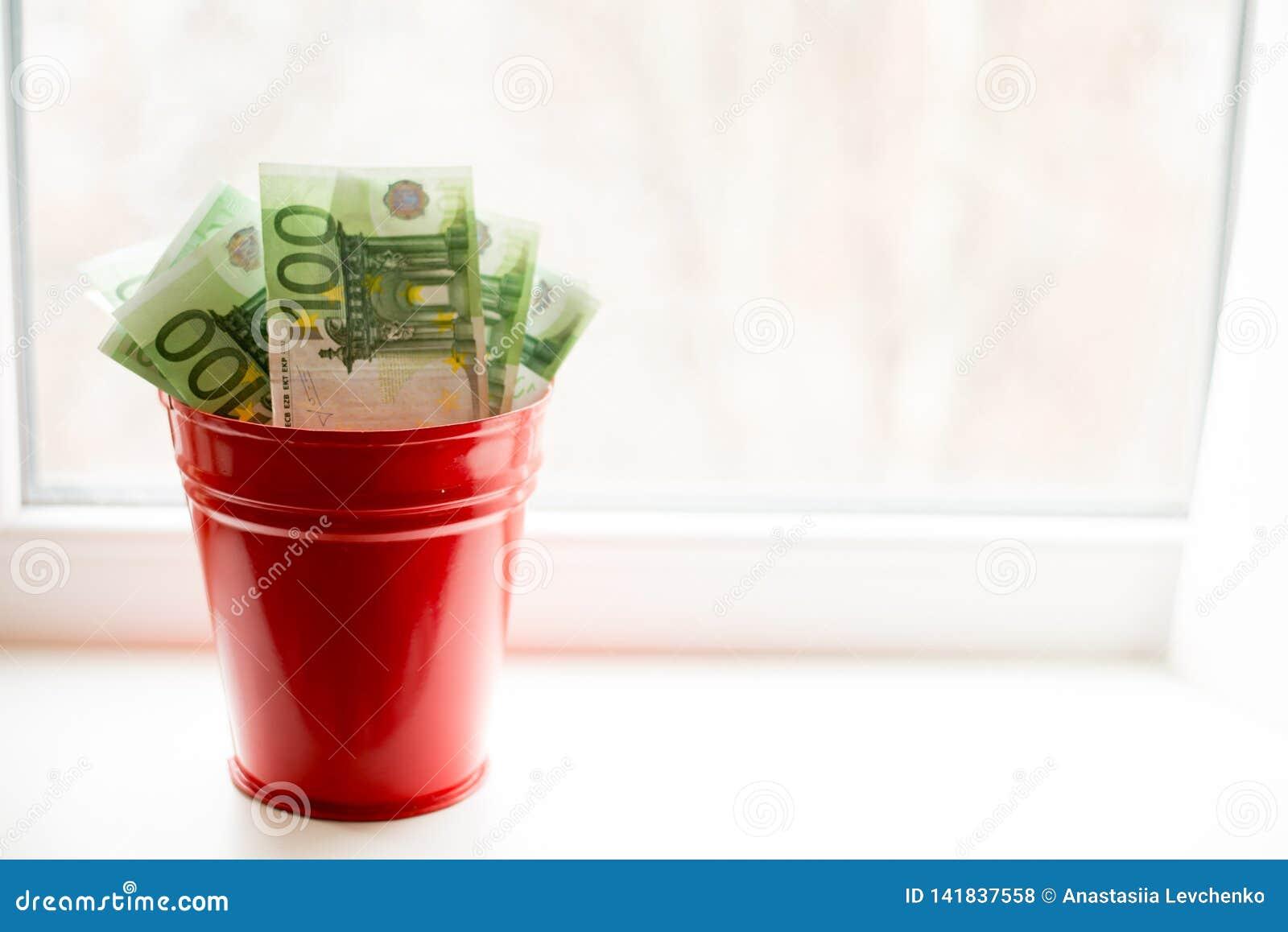 Moneybox, conta do Euro na cubeta na janela branca Fundo claro Lugar para o texto Muito dinheiro