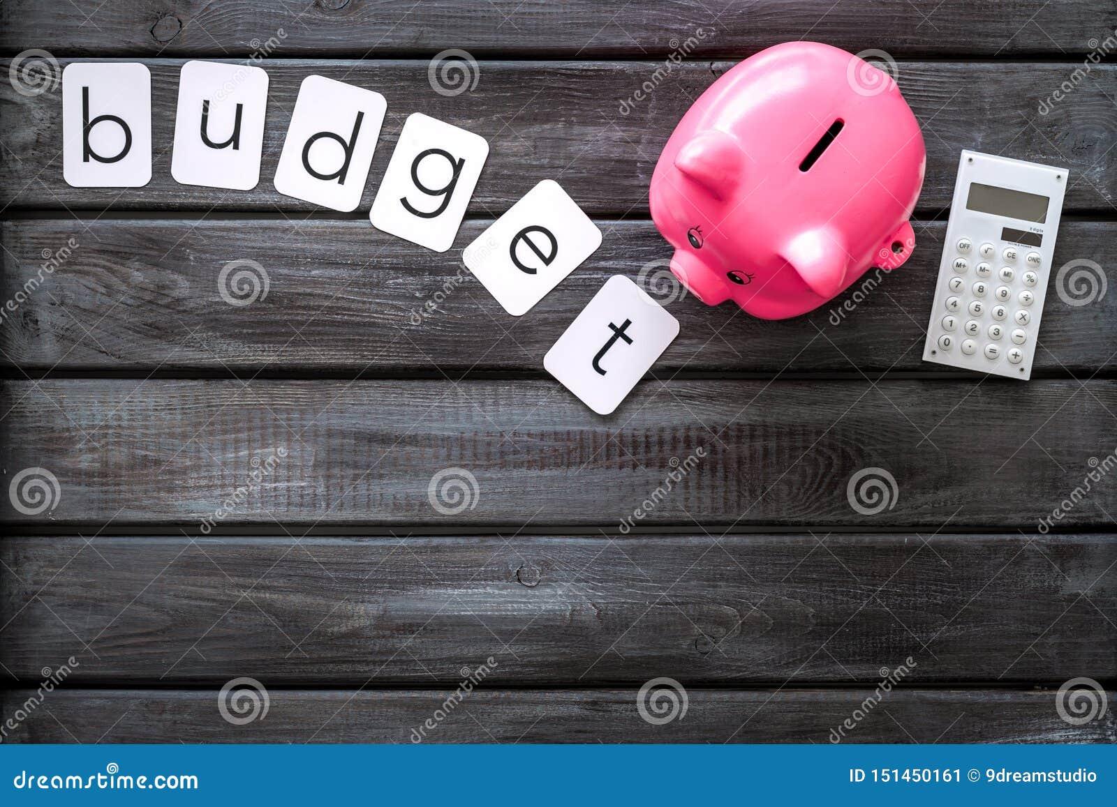 Moneybox en la forma del cerdo y de la calculadora para el presupuesto de negocio en maqueta de madera de la opinión superior del