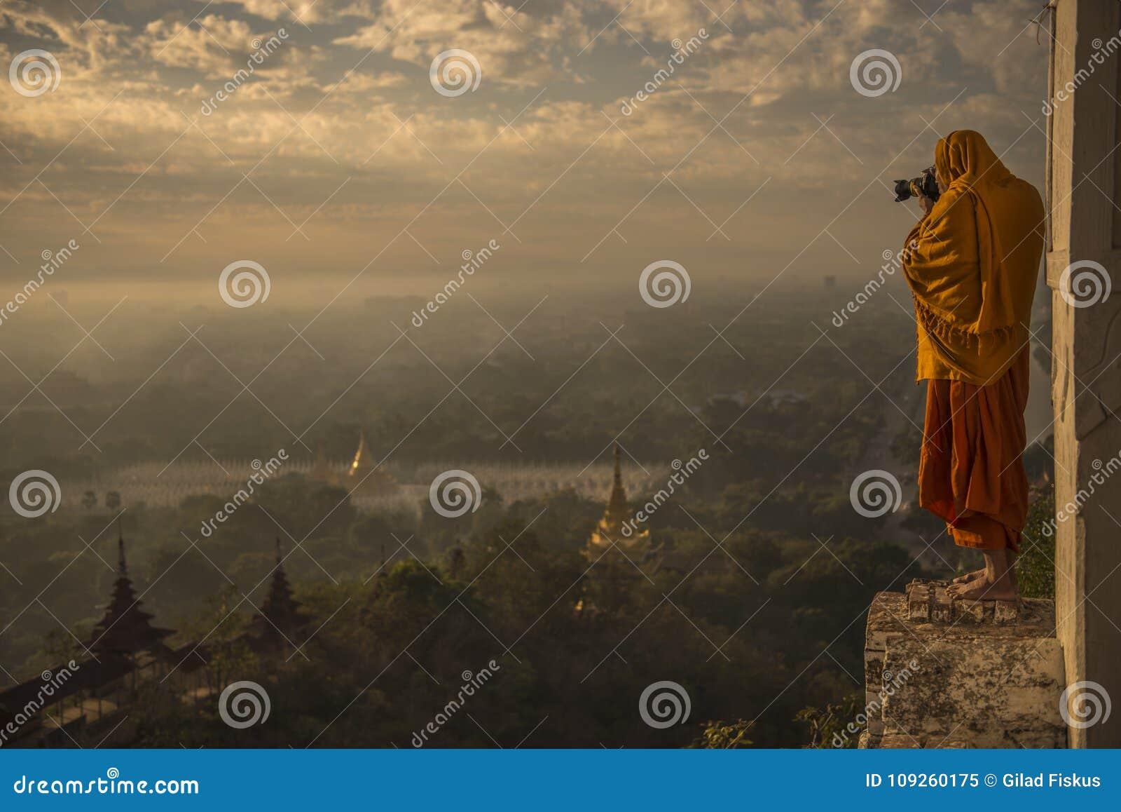 Monge que toma fotos no vale do nascer do sol de bagan