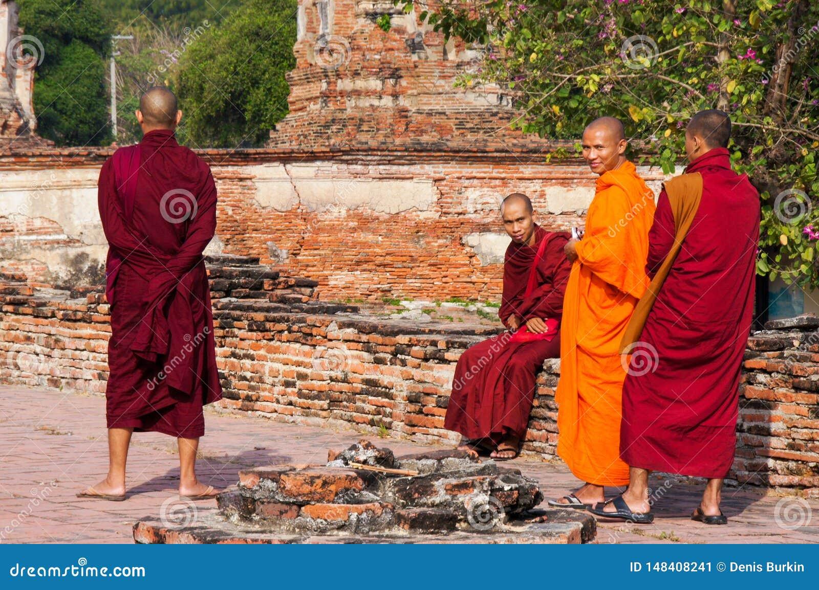 Monges budistas em vestes longas que andam no parque em Tail?ndia