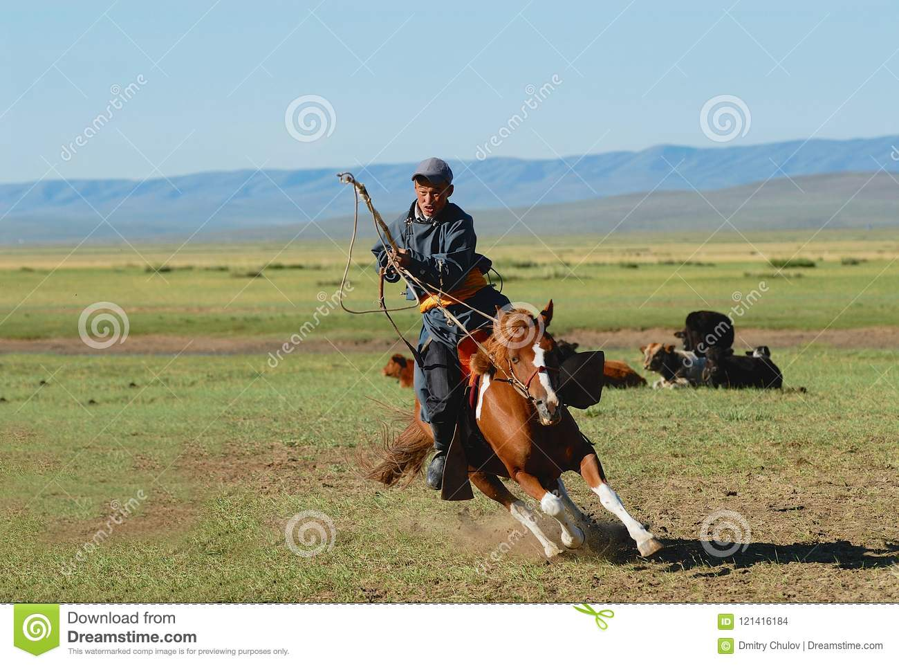 Mongolian man wearing traditional costume rides on horse back in a steppe in Kharkhorin, Mongolia.