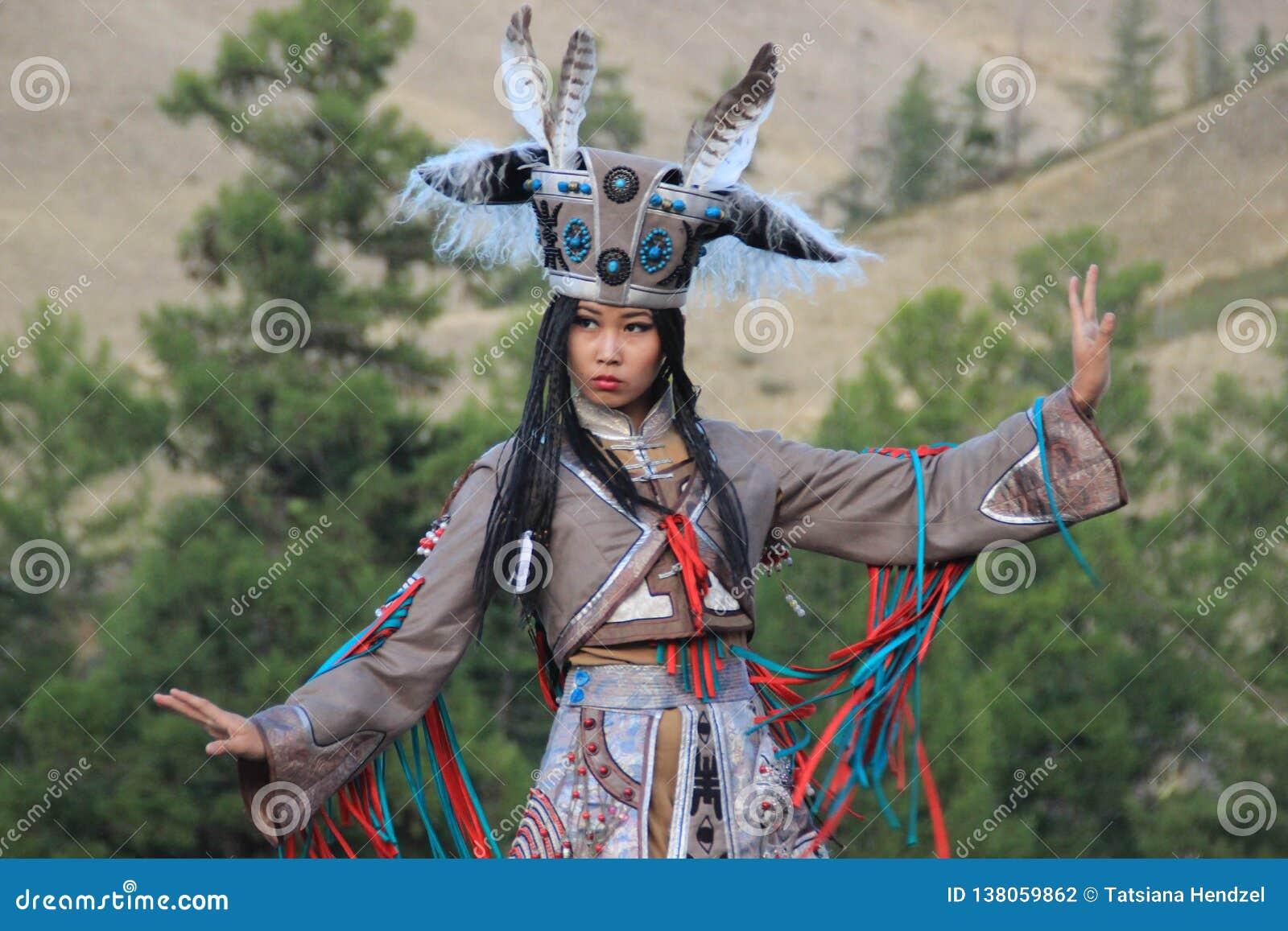 Mongolisk kvinna i medicinman- och häxadräktdanser på etapp i bergen Tyva folkdanser