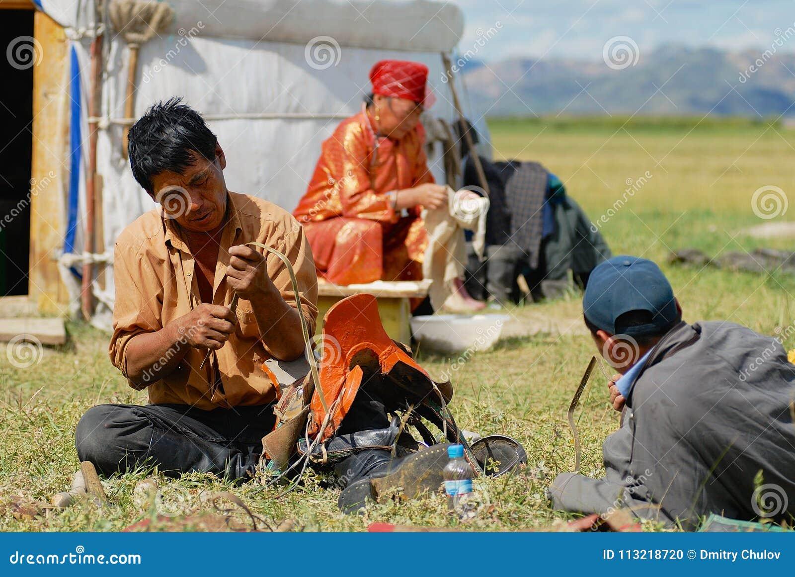 Mongolskiego członka rodziny dylemata konia tradycyjny comber i robi sprzątaniu przed jurta koczowniczym namiotem około Kharkhori