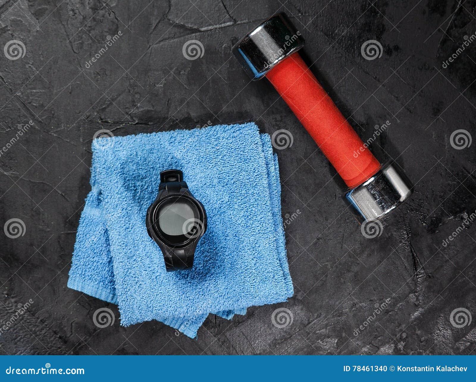Monitor da frequência cardíaca na toalha azul perto da bola de futebol