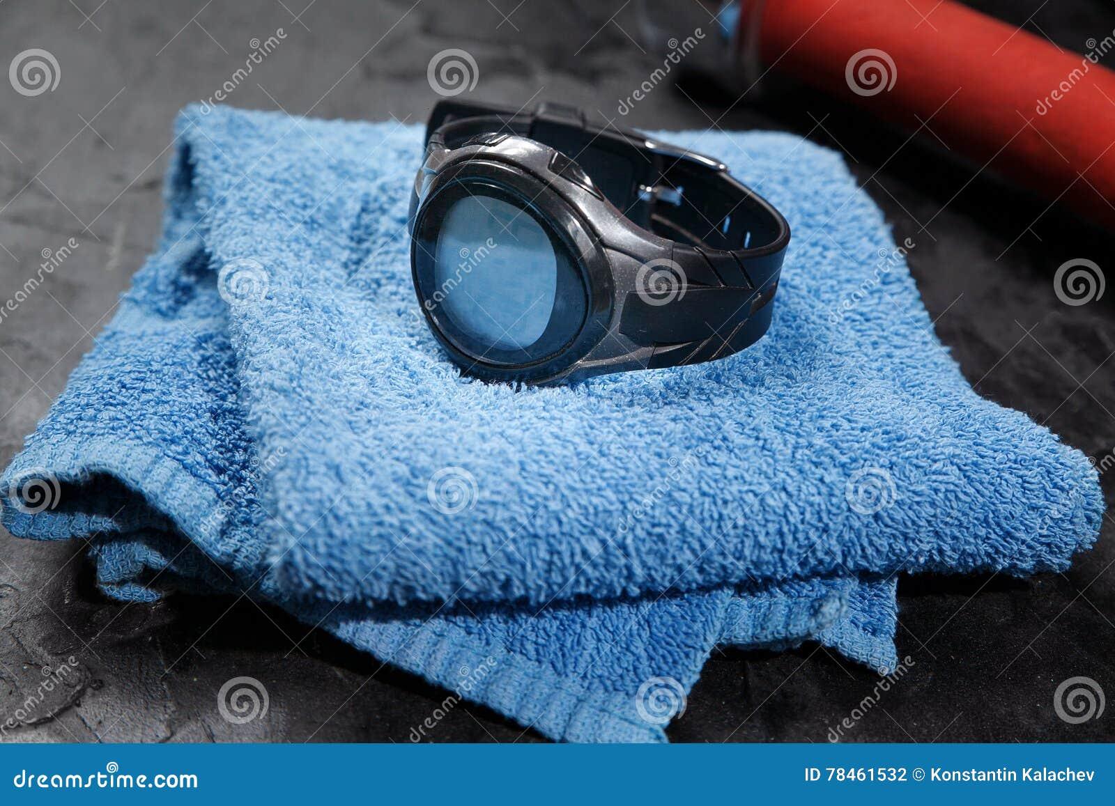Monitor del ritmo cardíaco en la toalla azul cerca del balón de fútbol
