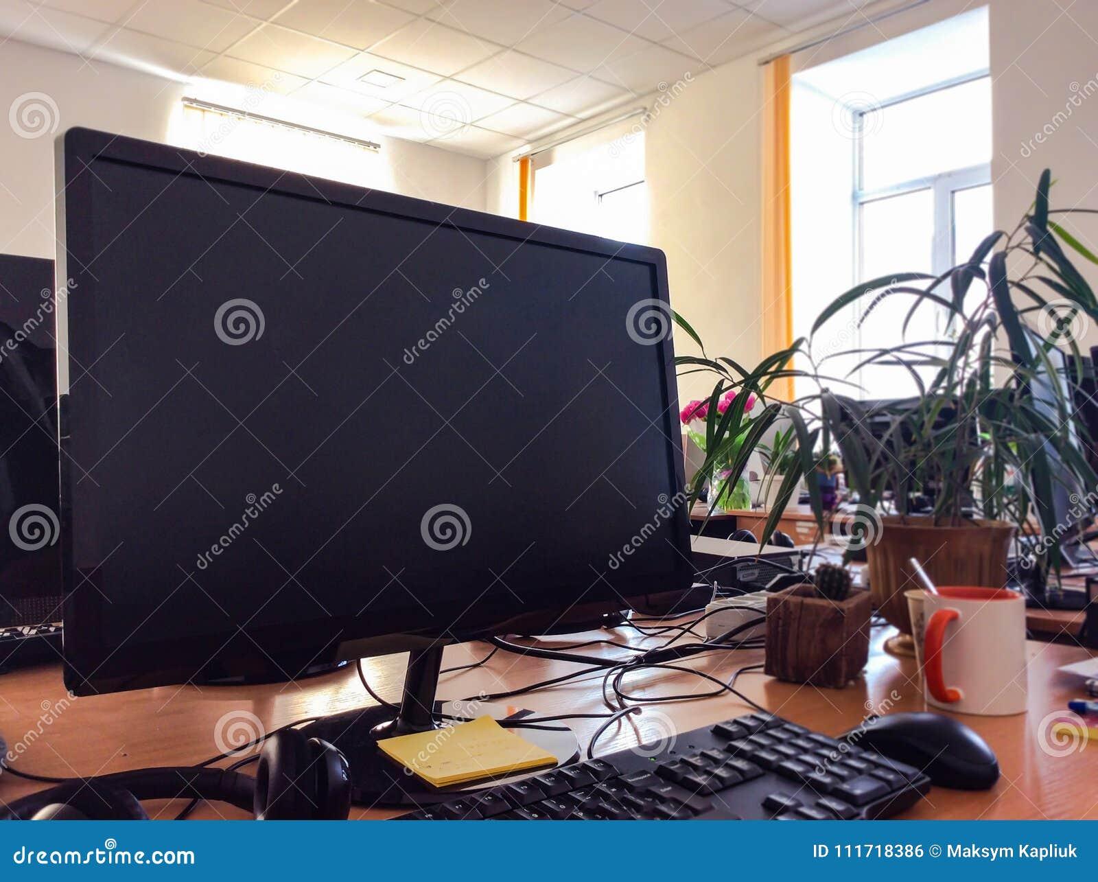 Monitor mit Tastatur auf Holztisch mit Tasse Kaffee und gre