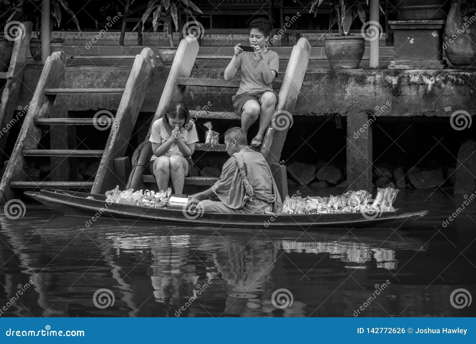 Monje Collecting Alms en el río de Amphawa