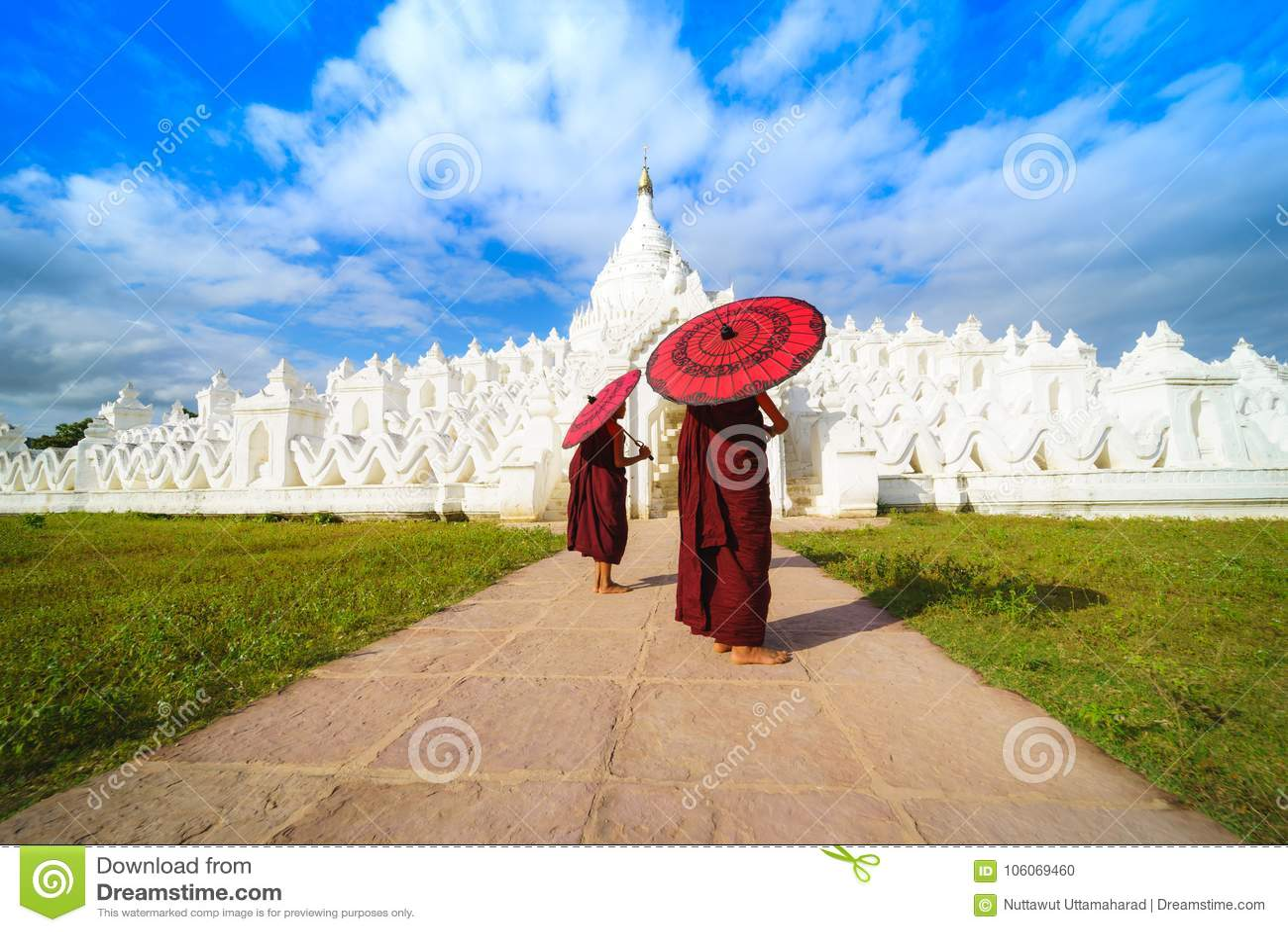 Monje joven asiático dos que sostiene los paraguas rojos en Mya Thein Tan