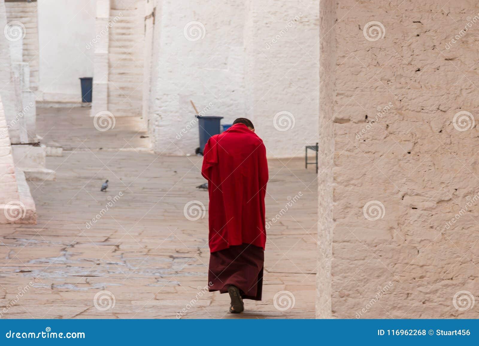 Monnik in rode robes in een klooster in Punakha, Bhutan