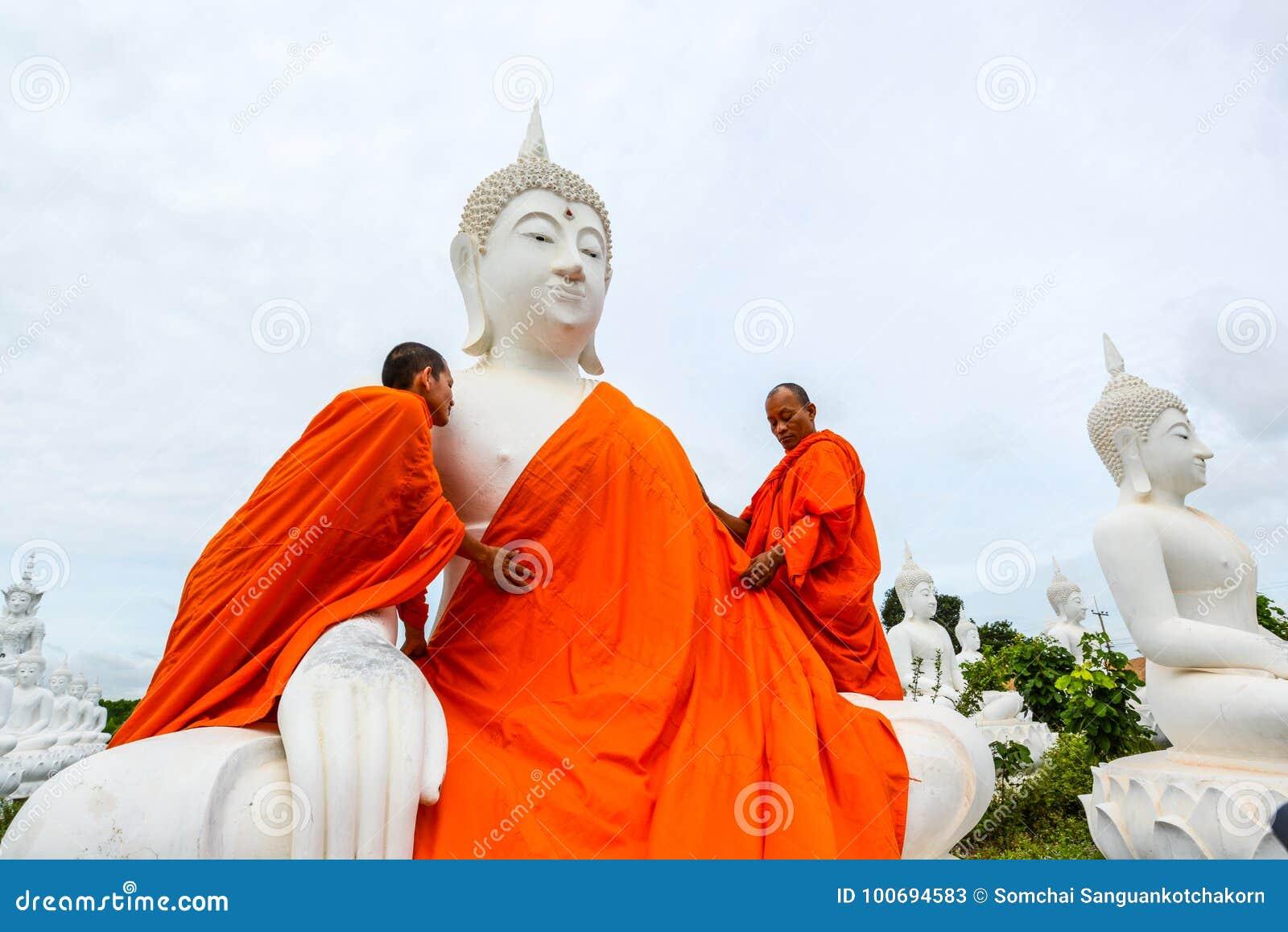 Monniken die één van het Witte Beeld van Boedha met robes kleden