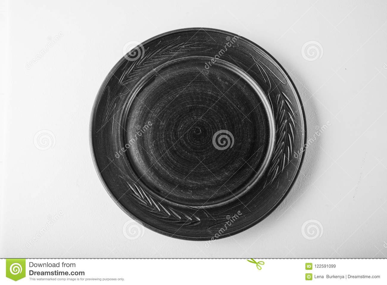Monochromatic image. Top view of a black pastel plate on a pastel white background. Minimalism food photography. Geometric style.