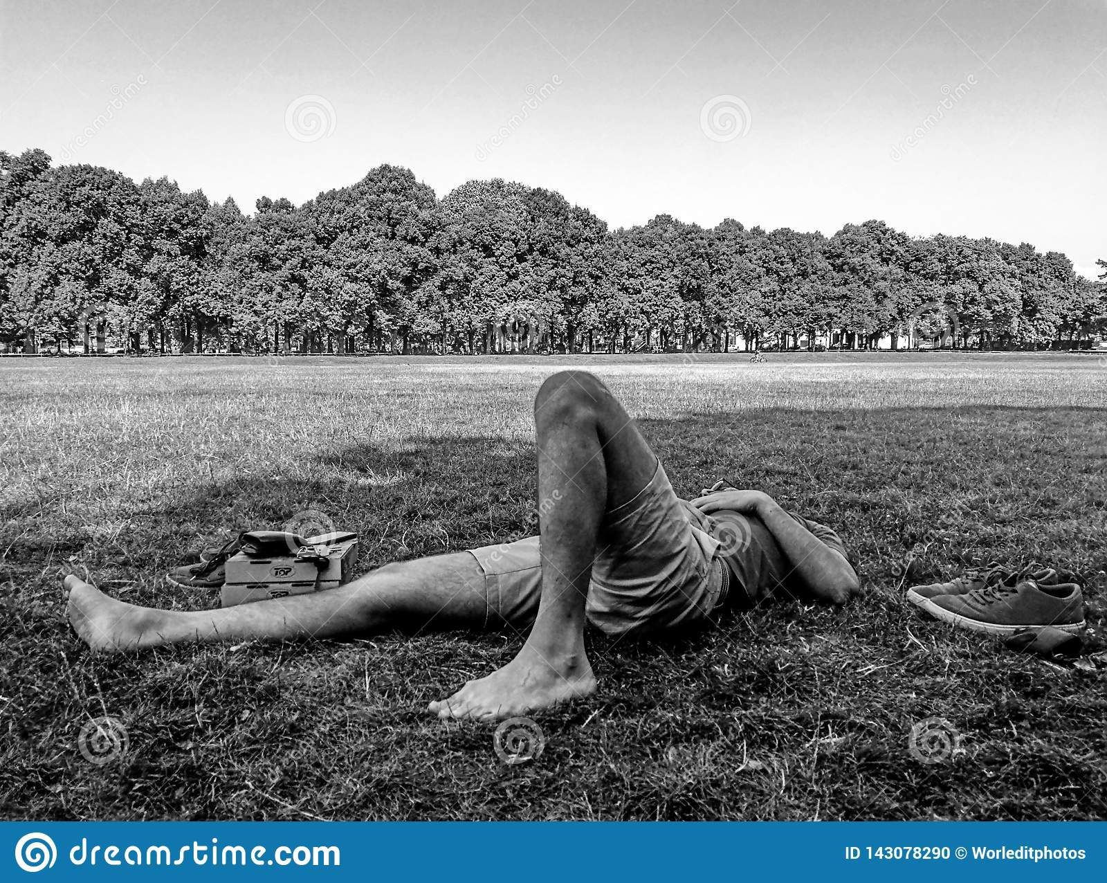 Young male skater resting on the grass with his eyes closed