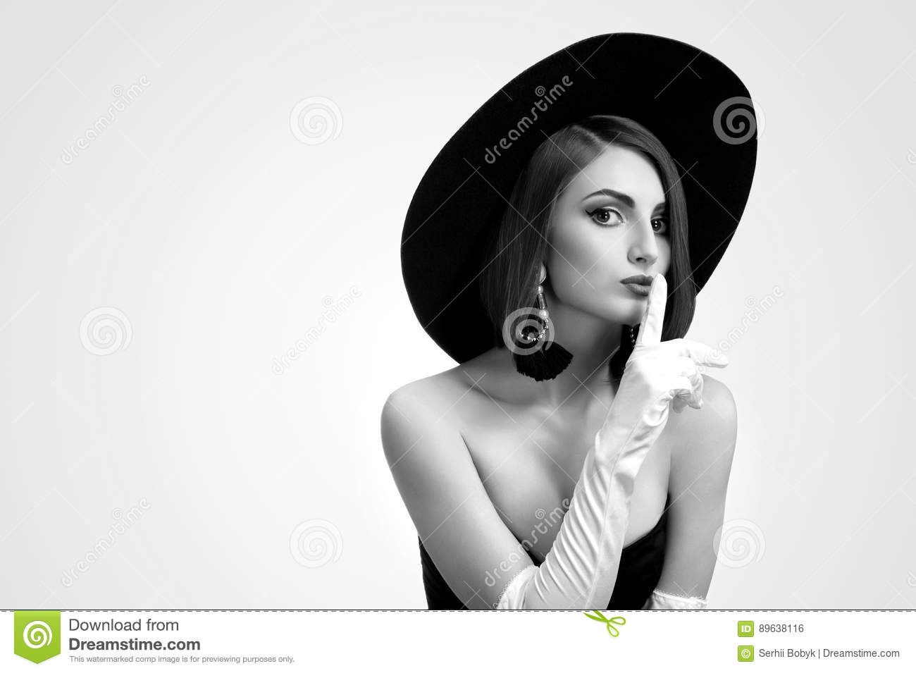 Black and white portrait of a beautiful elegant young fashion model shushing to the camera wearing a hat and gloves posing in a black dress copyspace