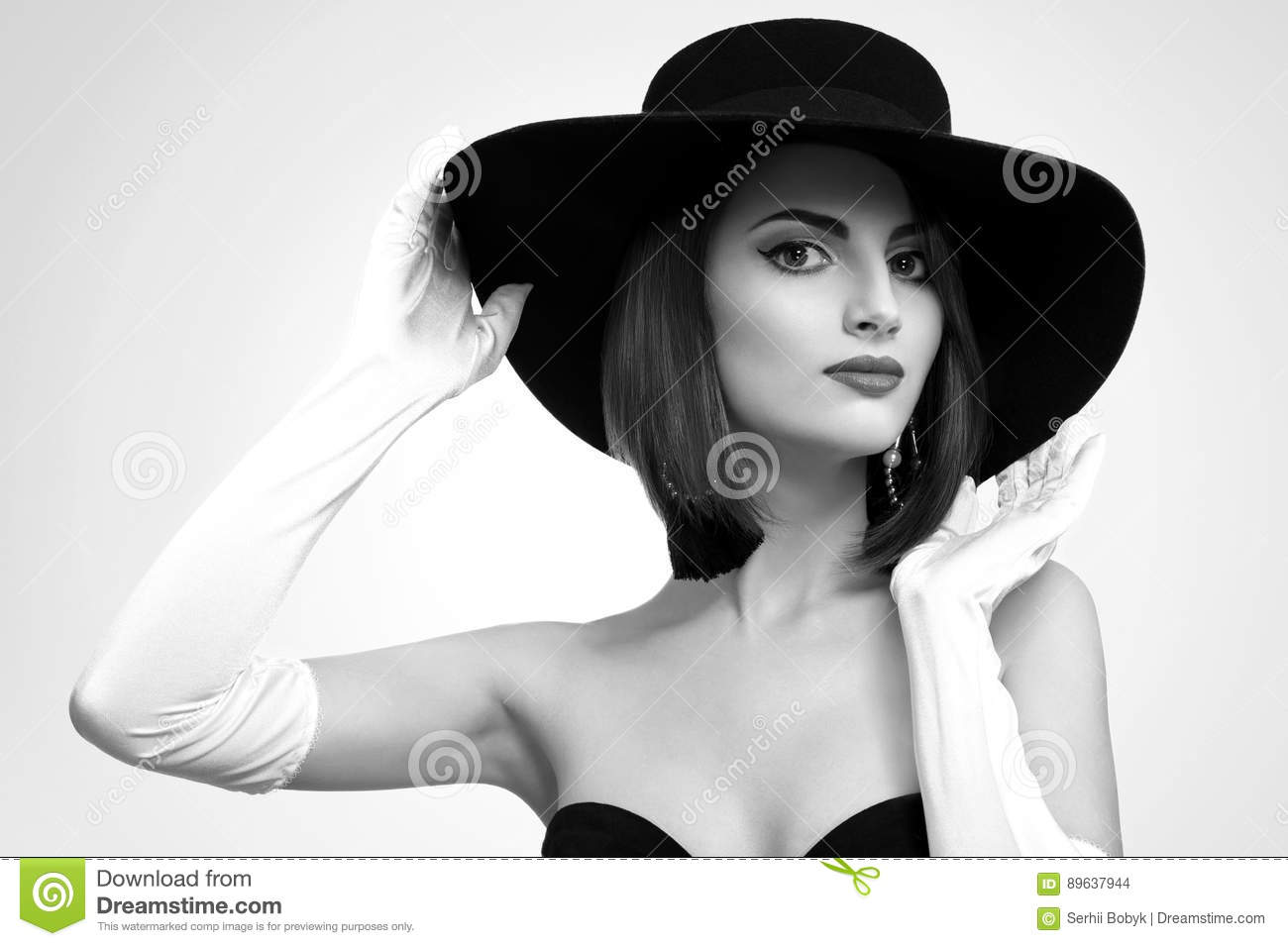 Black and white portrait of a stunning elegant woman in a black dress wearing a hat and gloves posing gracefully fashion modeling stylish retro vintage