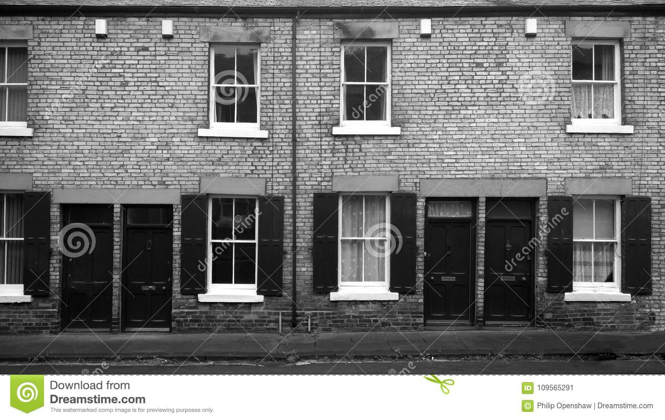Monochrome image of a row of typical northern english working class terraced houses with doors opening straight on to the street