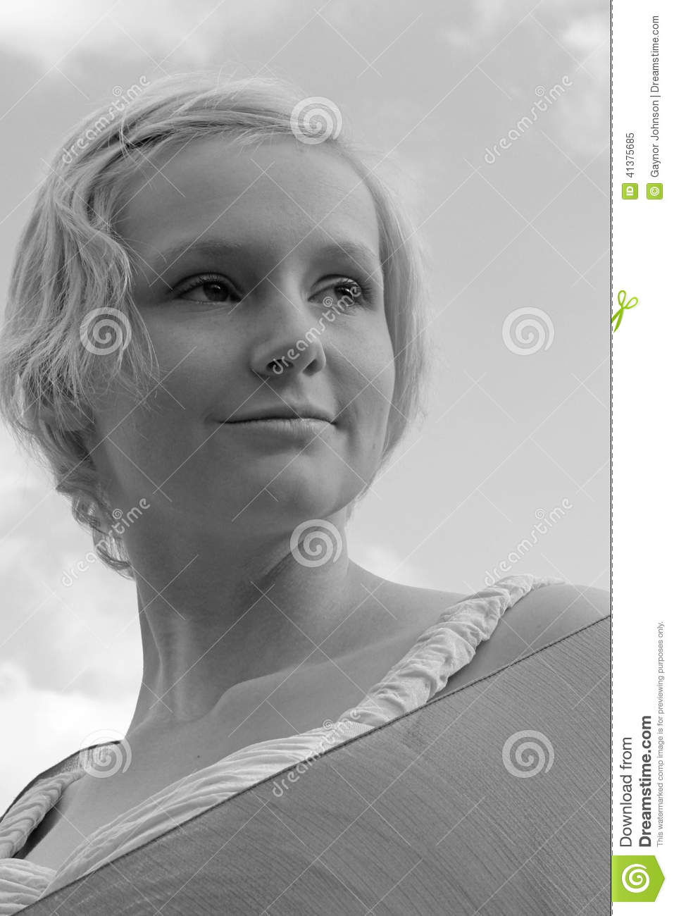 Monochrome image of young caucasian woman against a pale sky