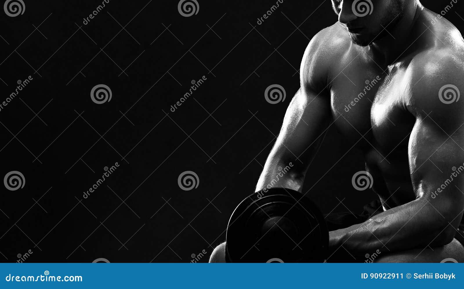 Monokromskott av en idrotts- riven sönder ung idrottsman med dumbb