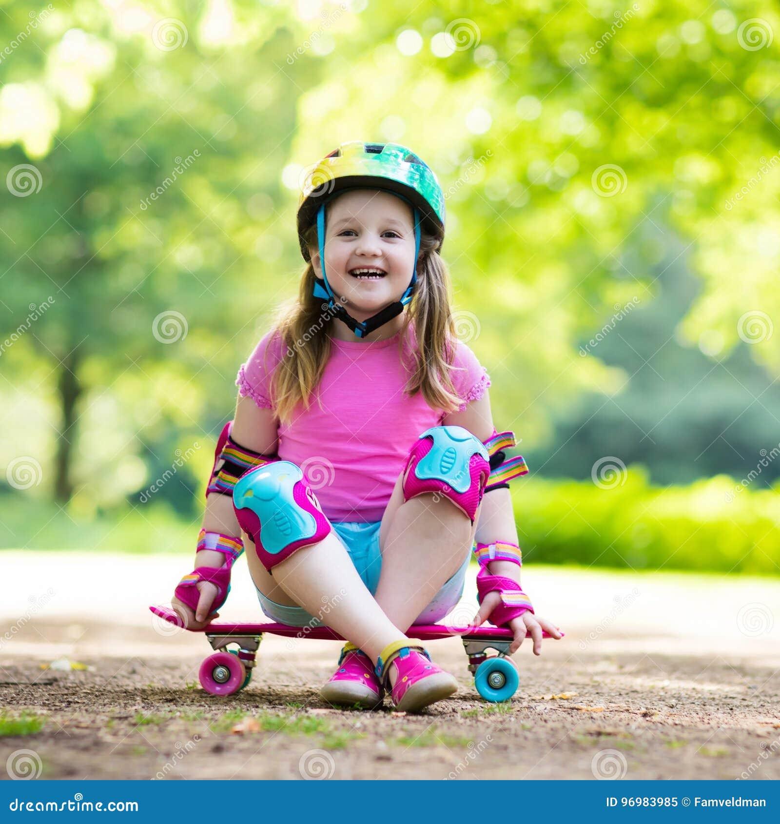 Monopatín del montar a caballo del niño en parque del verano