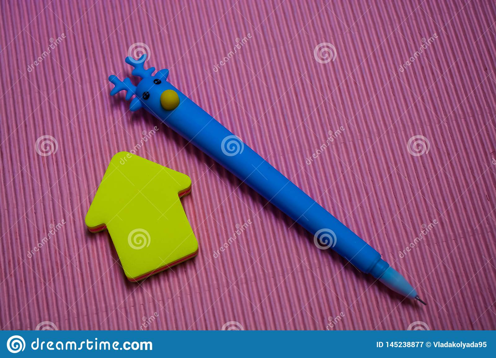 On monophonic bright pink background the unusual blue pen with the head of deer. Nearby lie stickers, note paper. Office.