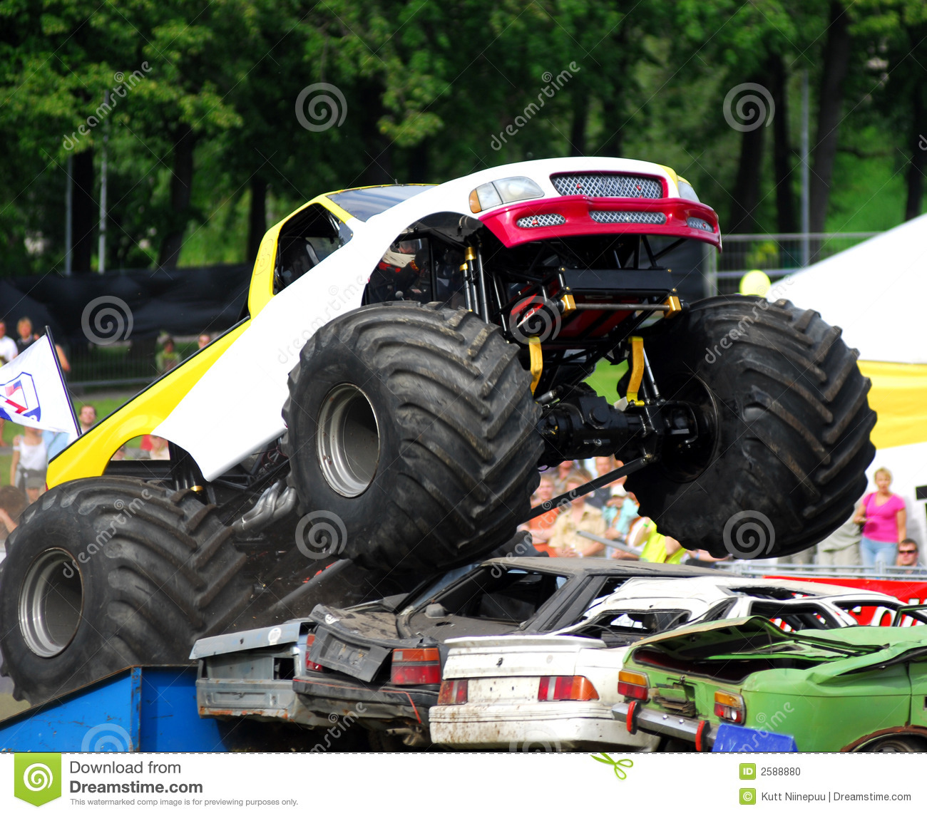 Monster truck rally, where an oversized truck jumps over wrecked cars.