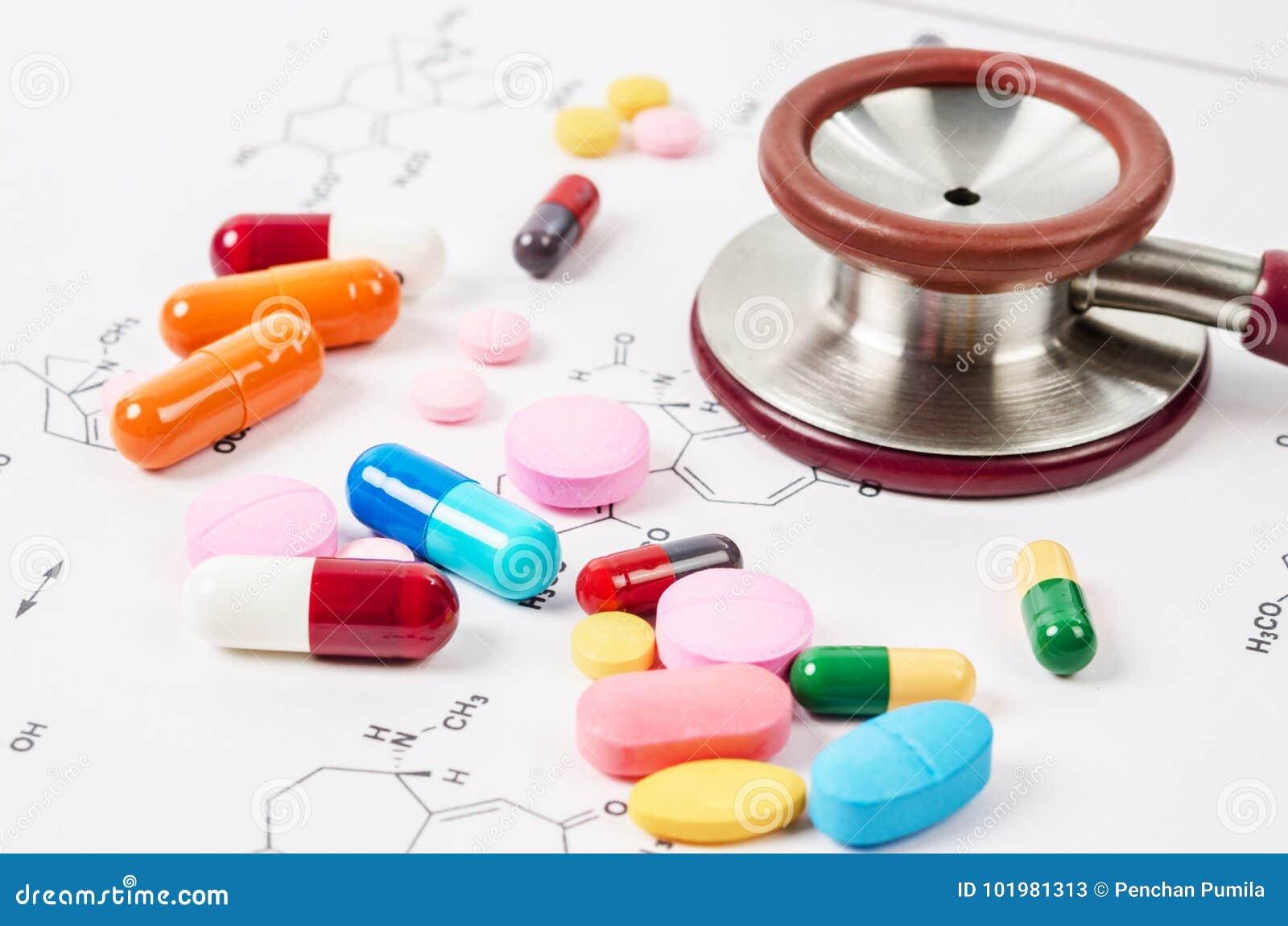 Montão de comprimidos e de tabuletas da cor com o estetoscópio médico
