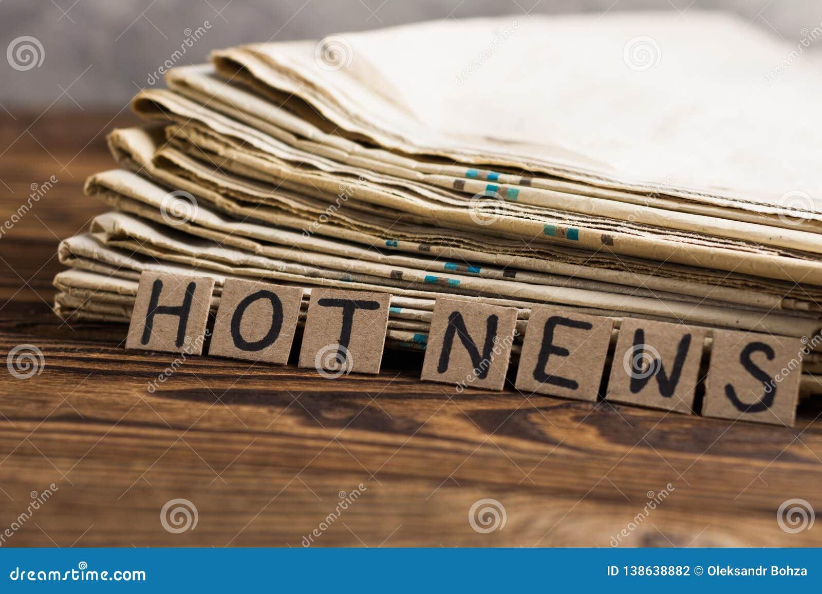 Montão de jornais velhos ao lado dos quadrados do retângulo do cartão com novidades escritas à mão da inscrição na tabela de made