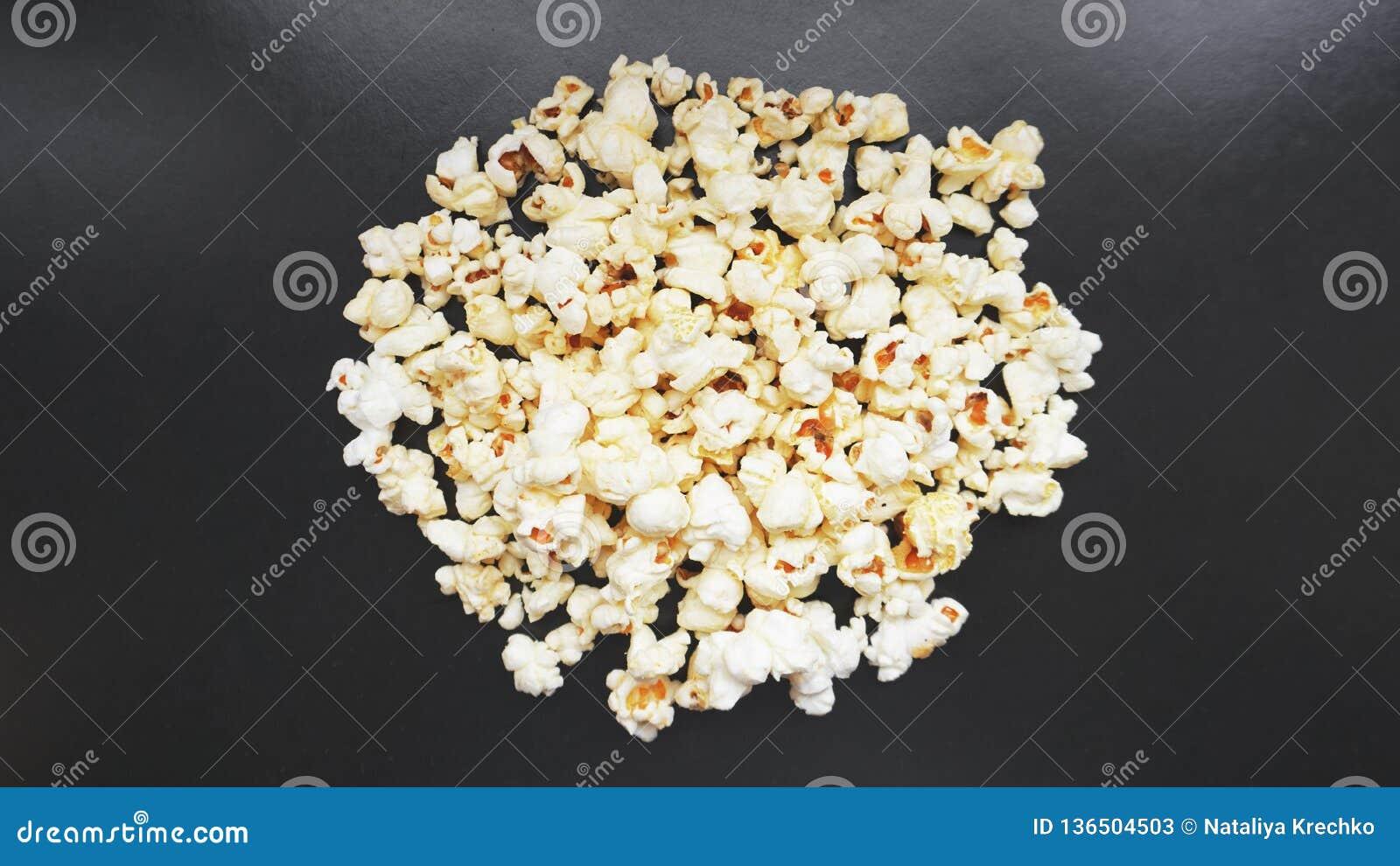 Montón de las palomitas saladas clásicas en fondo negro Cine o comida del concepto