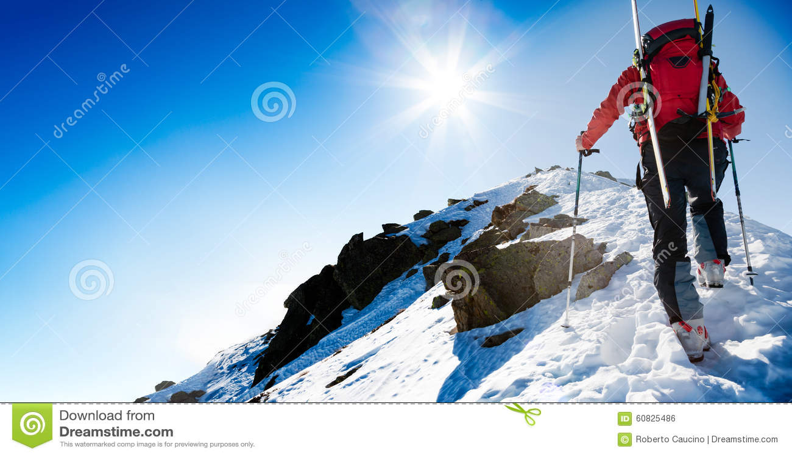 Montañés del esquí que camina para arriba a lo largo de un canto nevoso escarpado con SK