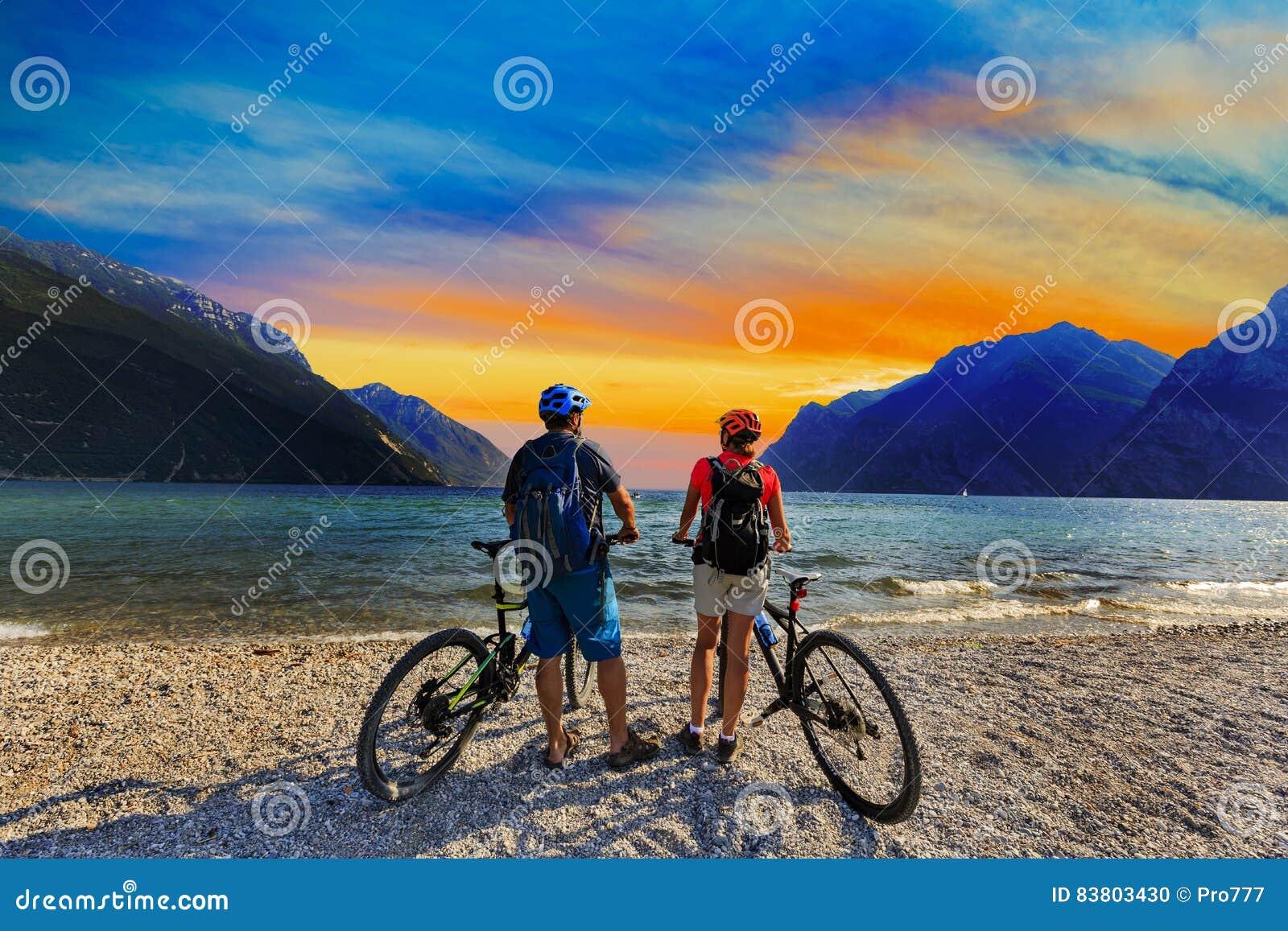 Montaña biking, par con las bicis en la puesta del sol en el lago Garda, Riva