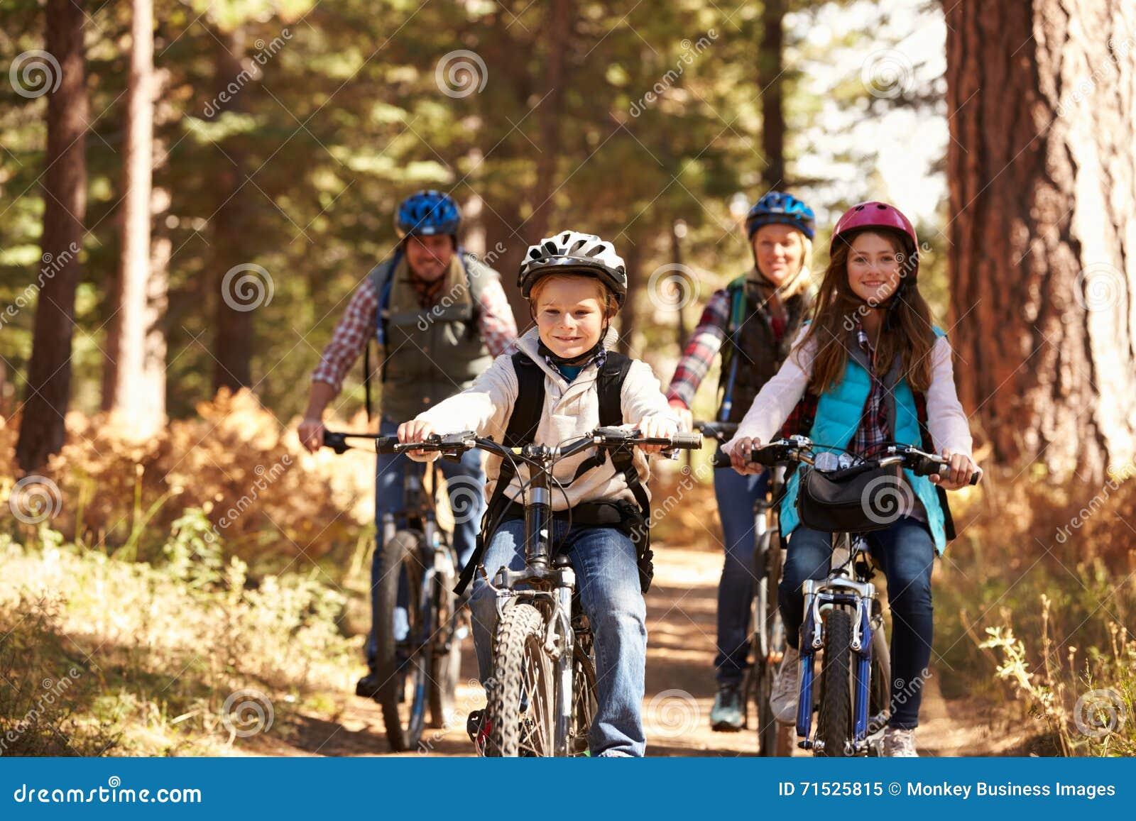 Montaña de la familia biking en el rastro del bosque, vista delantera