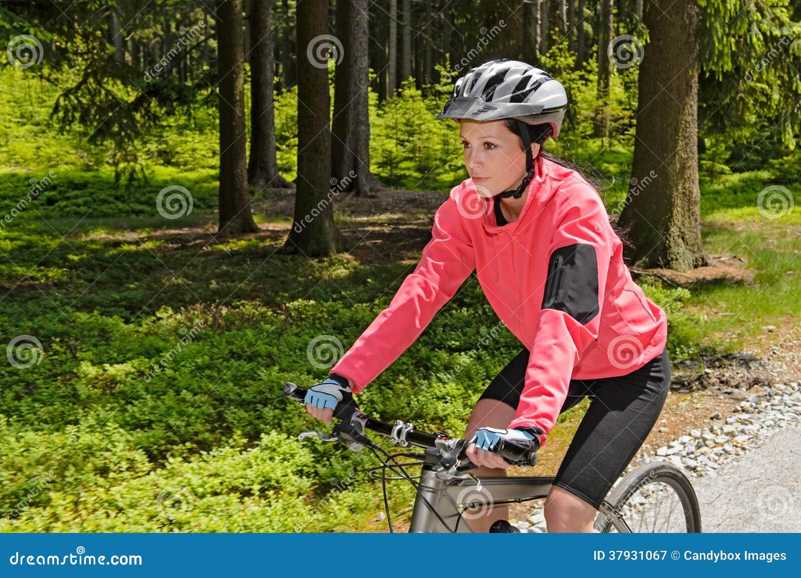Montaña de la mujer biking en día soleado del bosque