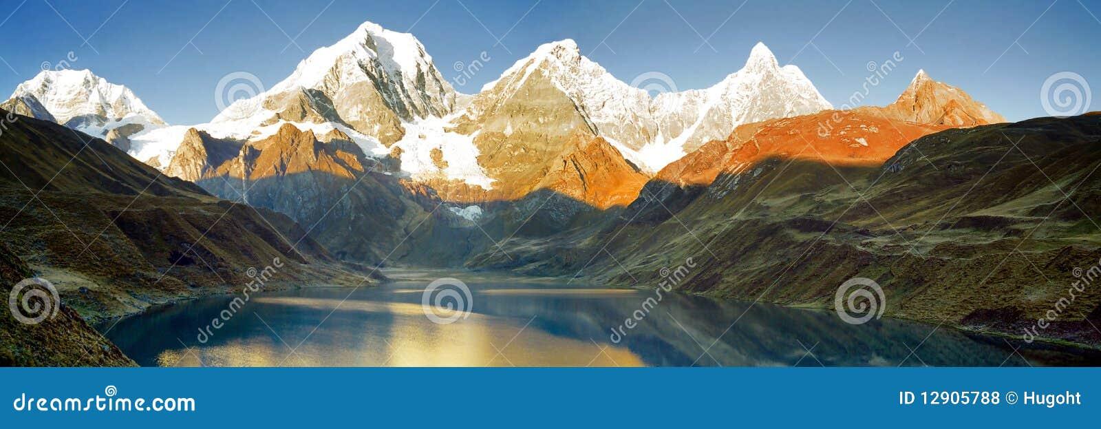 Montañas que reflejan en el lago en la salida del sol