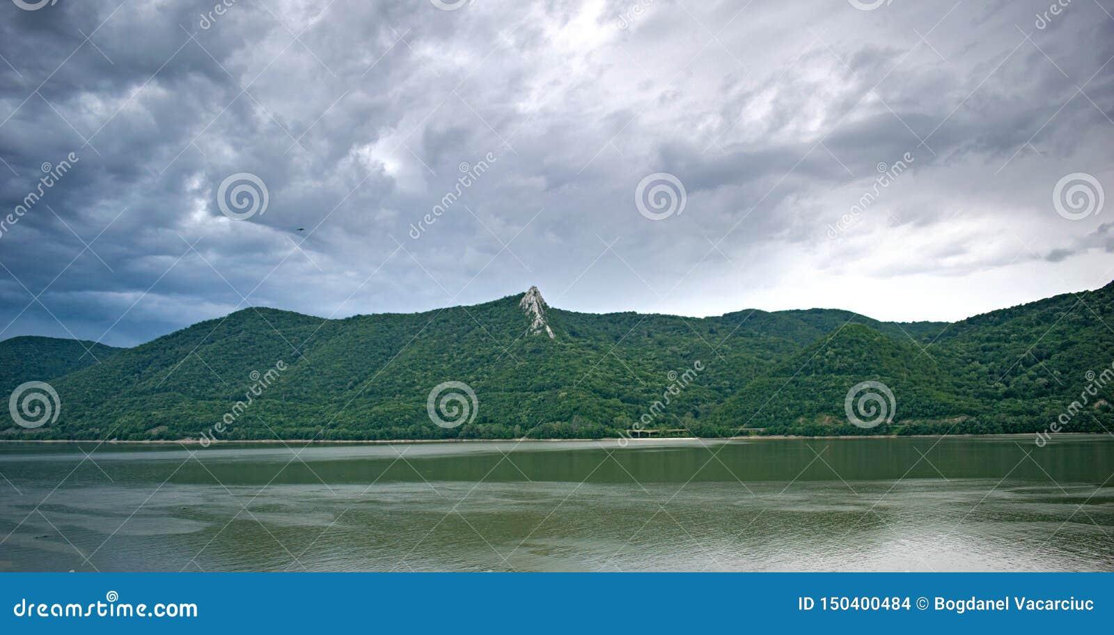 Montañas, un gran río y un cielo con muchas nubes negras