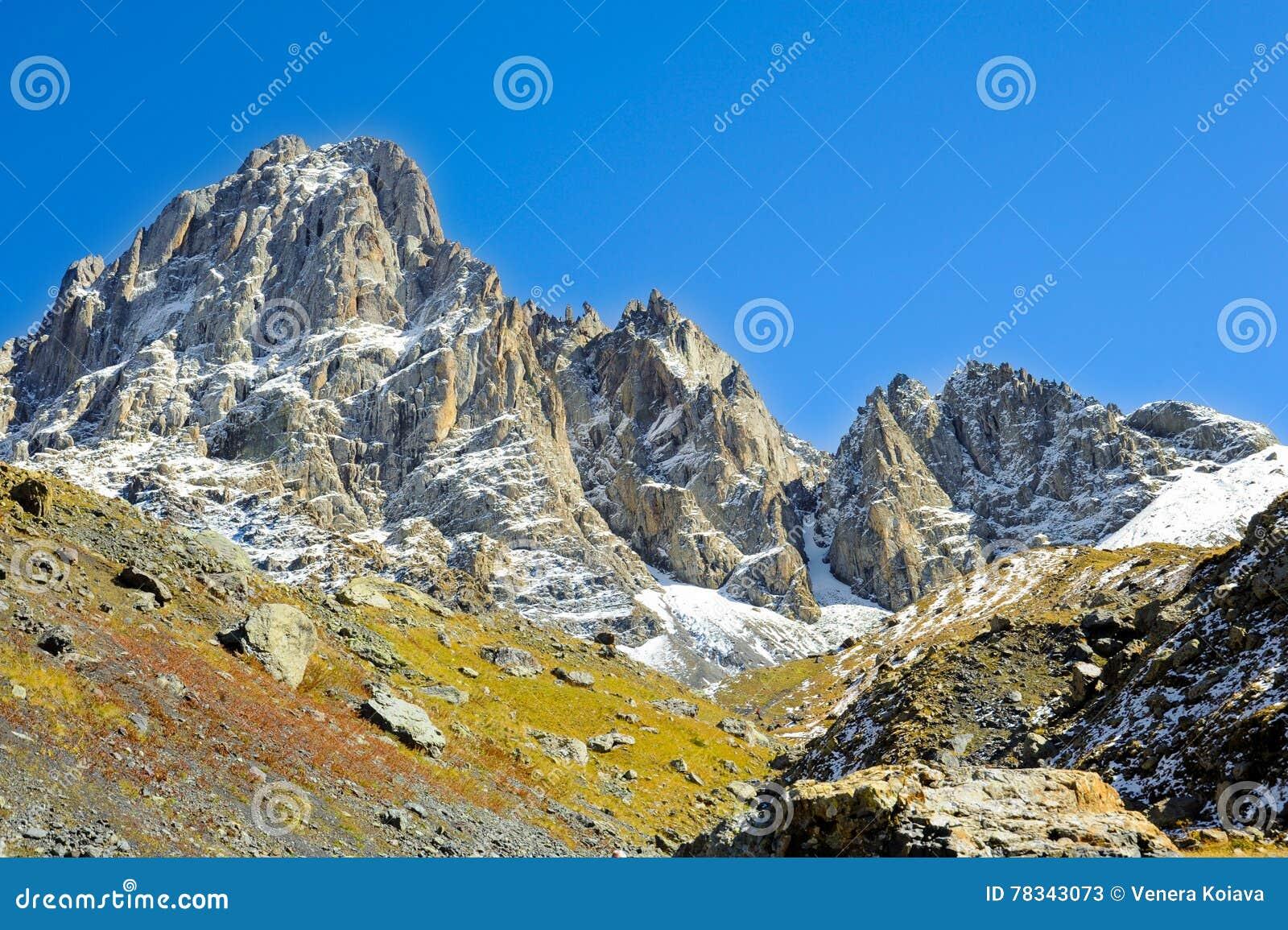 Montagne di Caucaso, villaggio Juta collina verde, cielo blu e picco nevoso Chaukhebi di estate