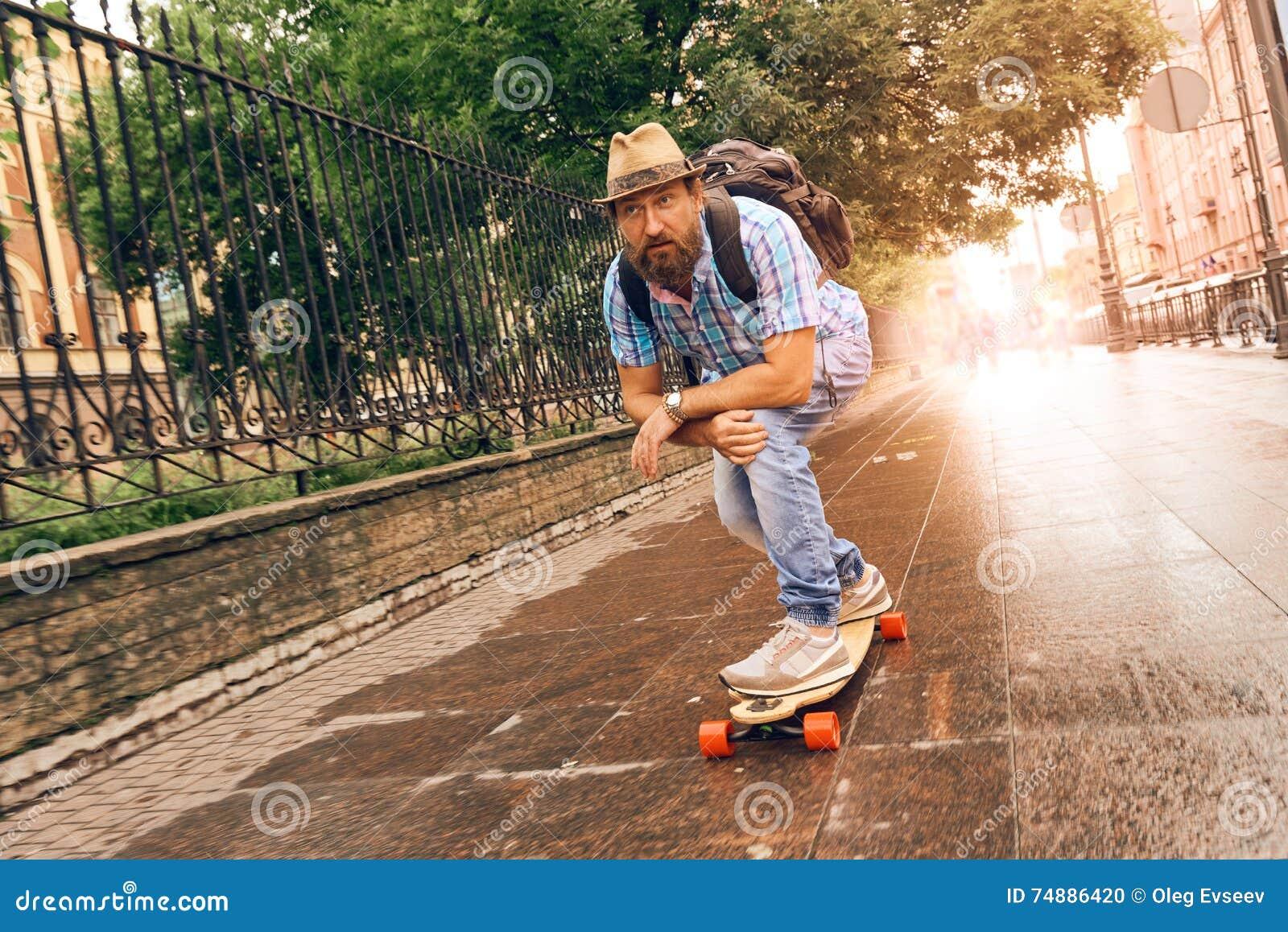 Montando no longboard nas ruas urbanas, ajuste do conceito do estilo de vida