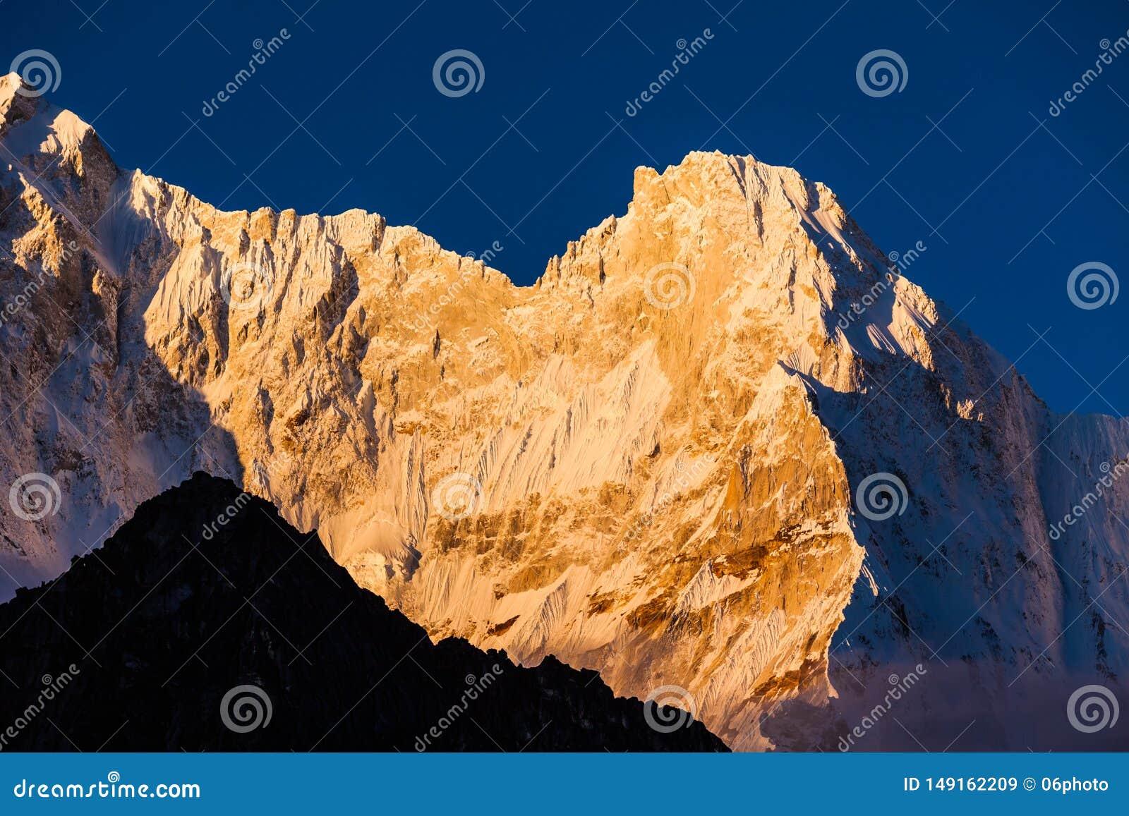 Montanha ascendente pr?xima da neve no nascer do sol na montanha de Himalaya de Tibet
