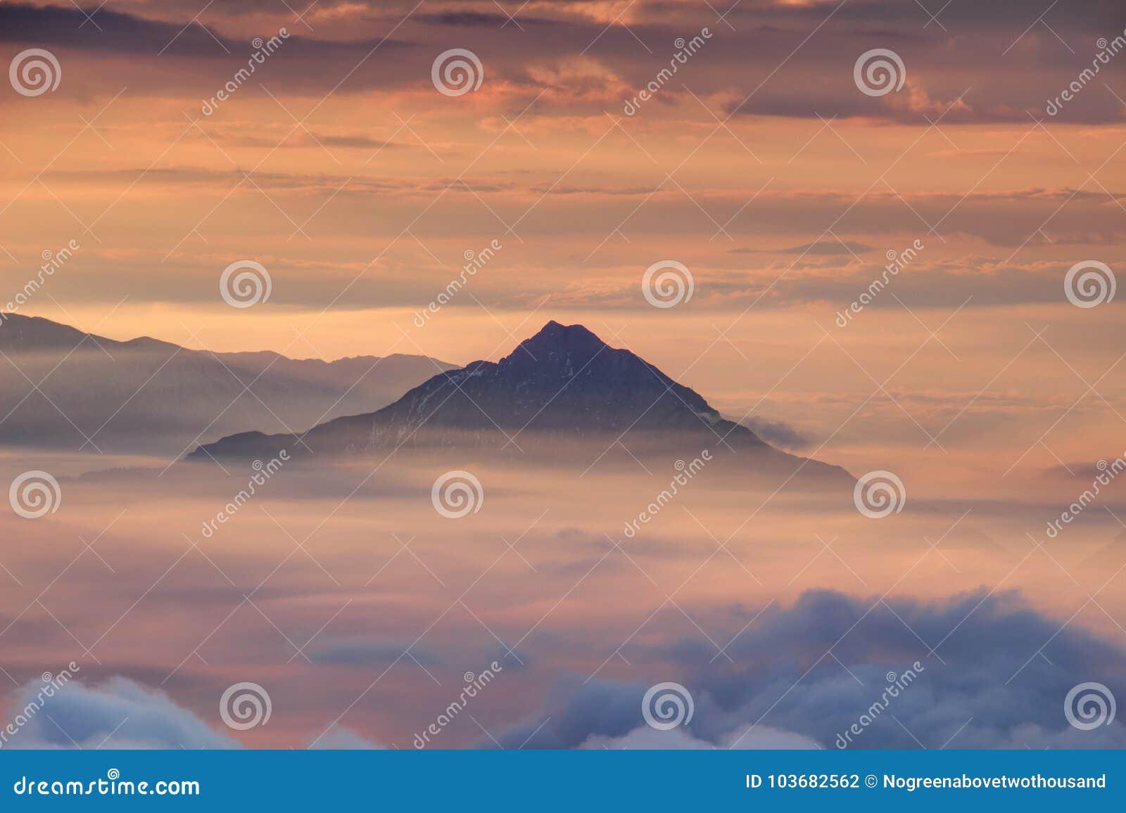 Montanha cônica só acima da névoa e das nuvens da manhã