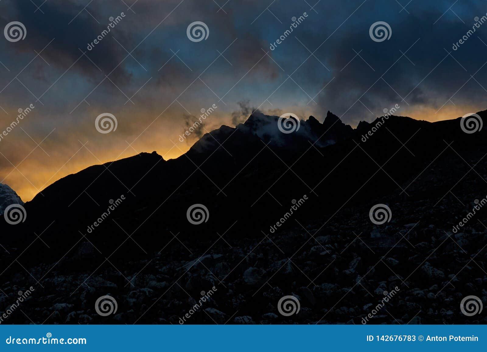 A montanha Himalaia enorme com geleiras em Nepal cobriu por nuvens antes do nascer do sol