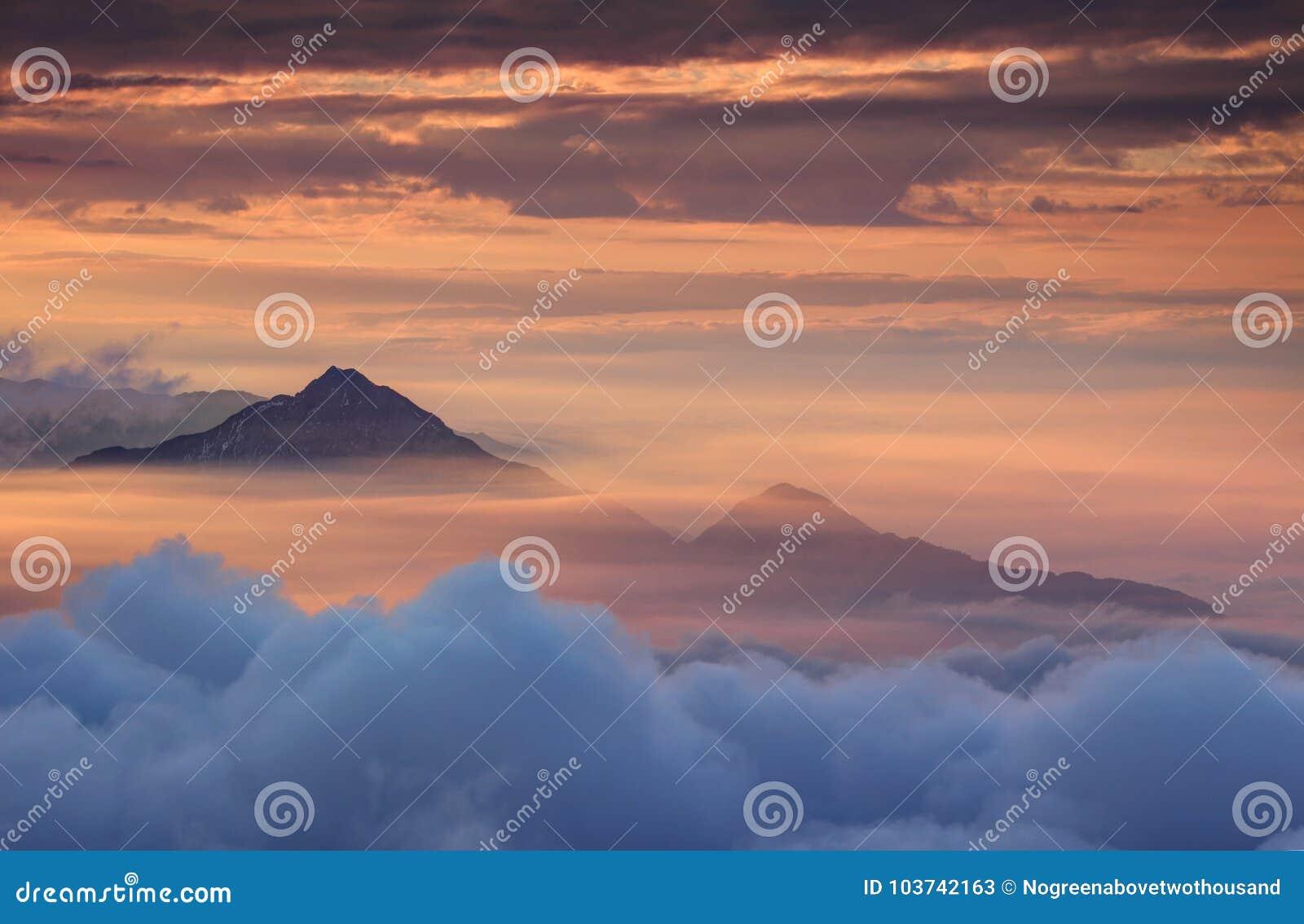 Montanhas cônicas na névoa do outono e no céu vermelho na manhã