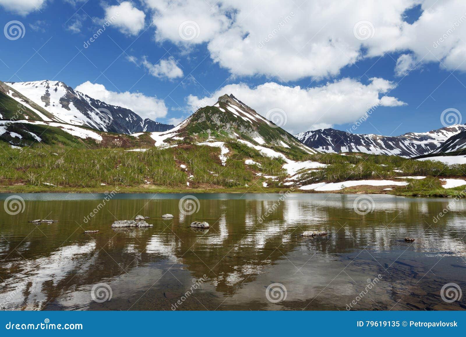 Montanhas, lago e nuvens de Kamchatka no céu azul no dia ensolarado
