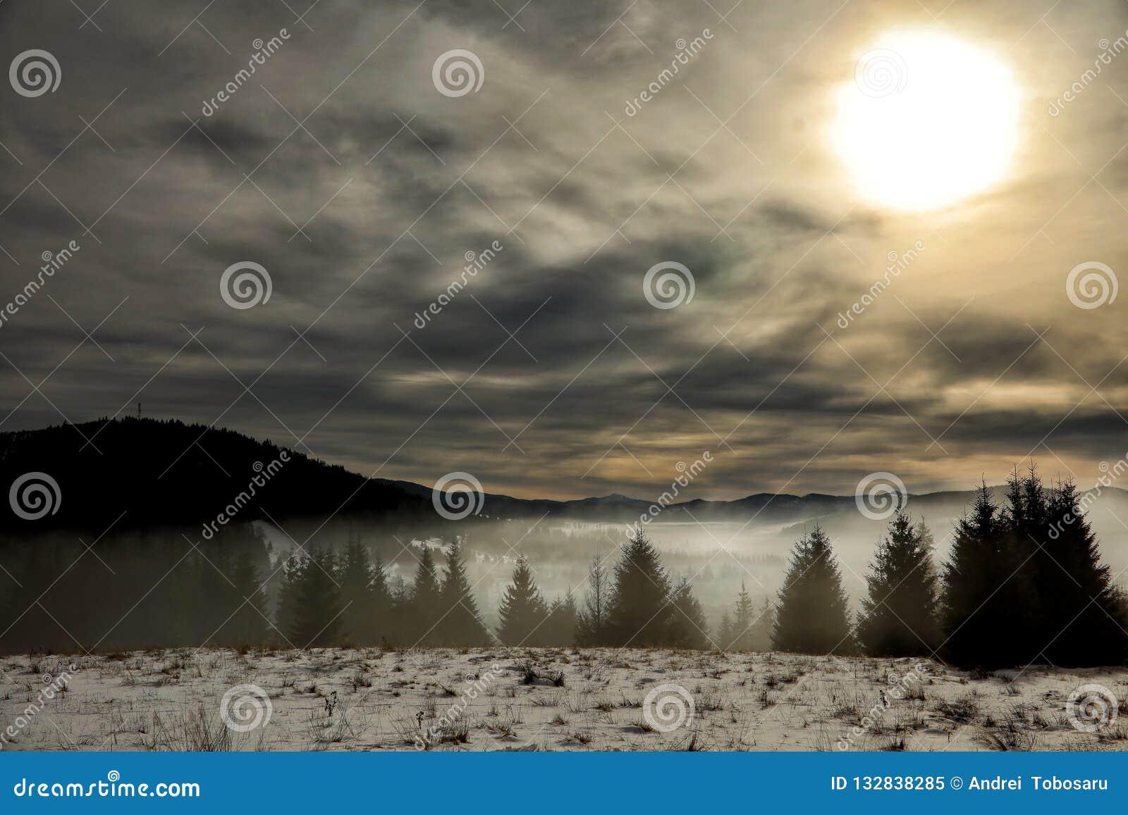 Montanhas romenas em uma tarde nevoenta