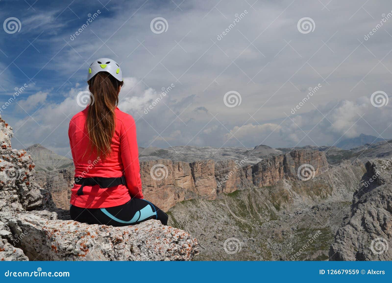 Montanhista da mulher que senta-se no pico de montanha
