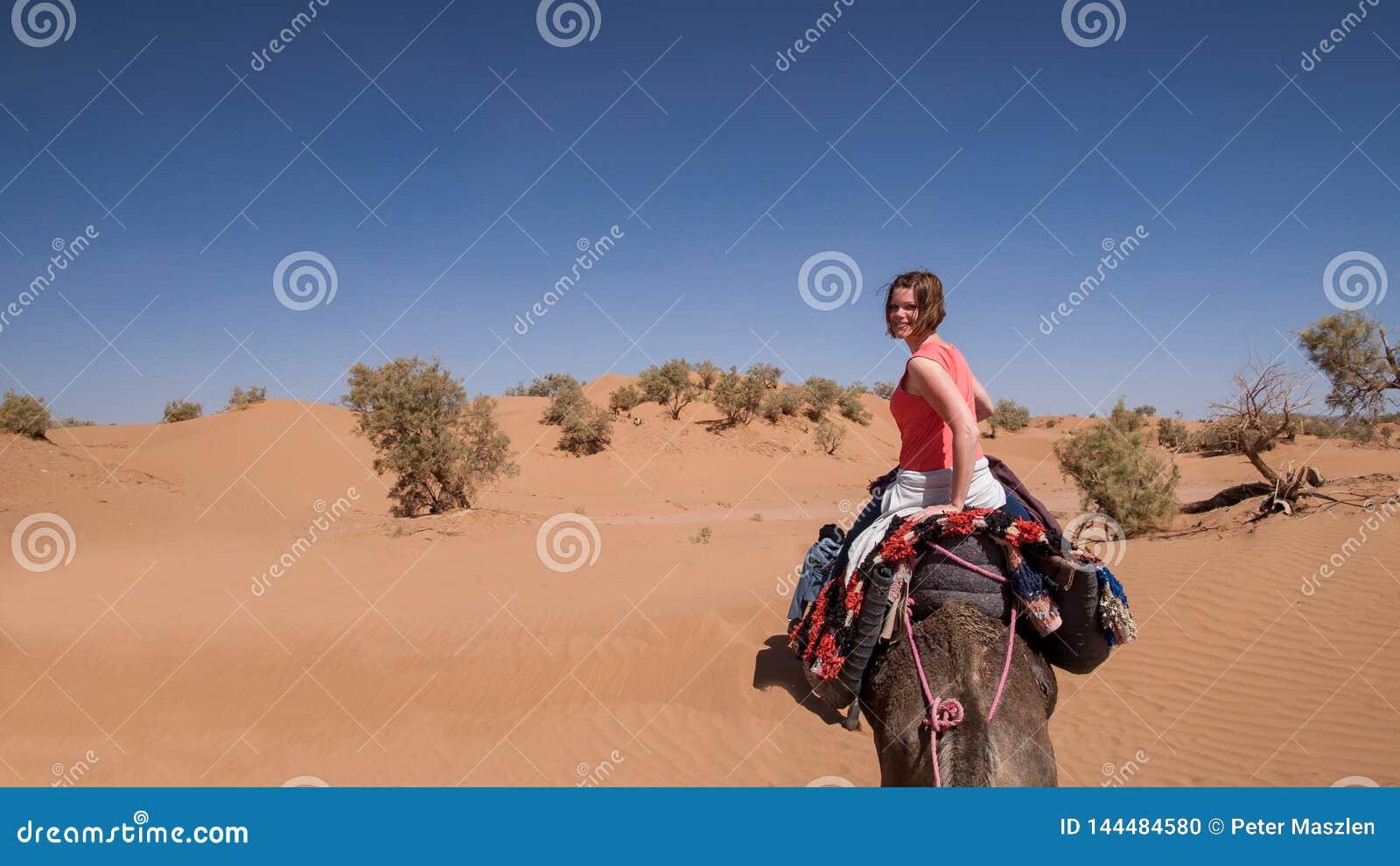 Montar a caballo de la mujer joven en un dromedario en el desierto marroquí de la arena