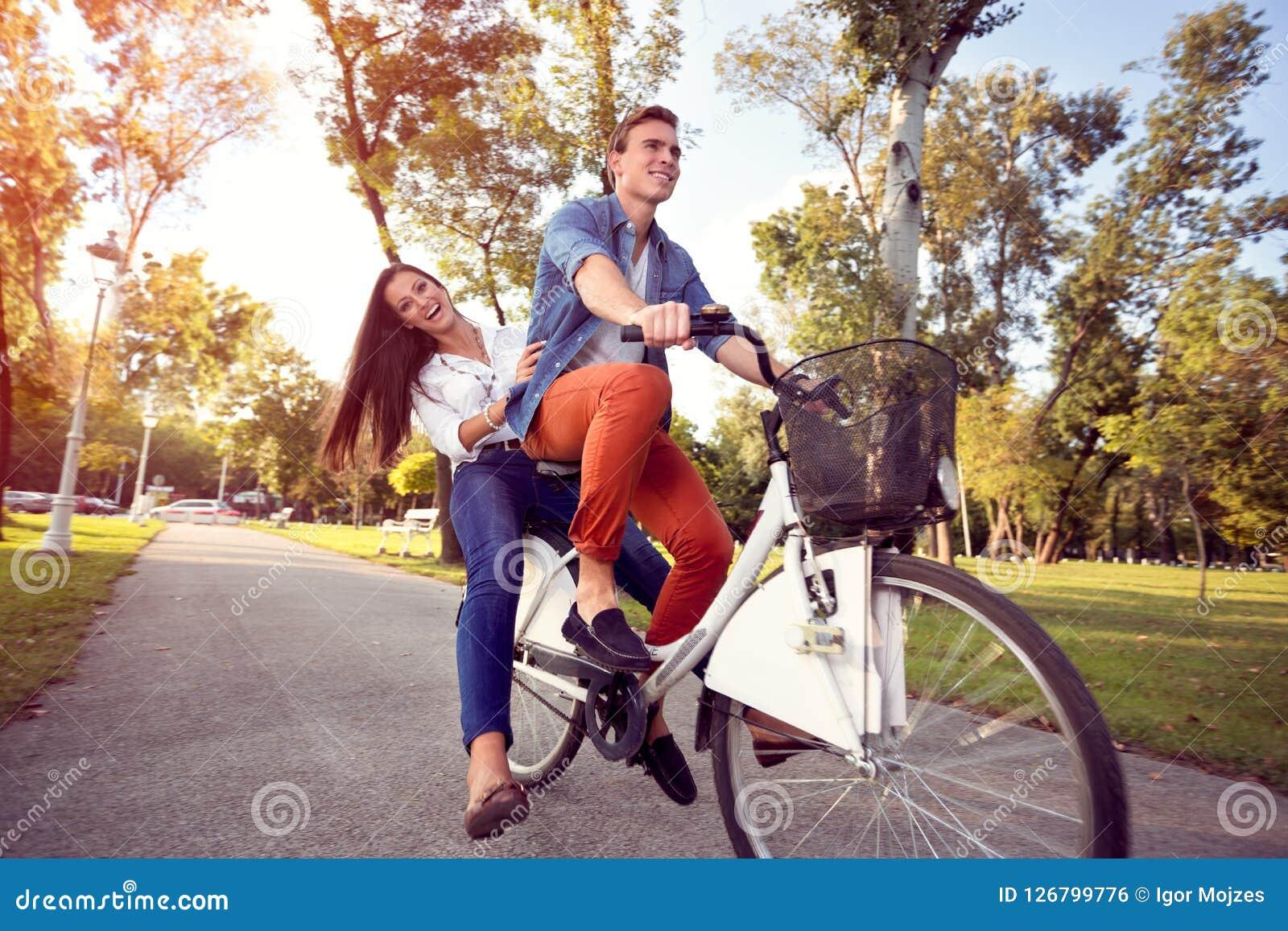 Montar a caballo divertido feliz de los pares el otoño de la bicicleta